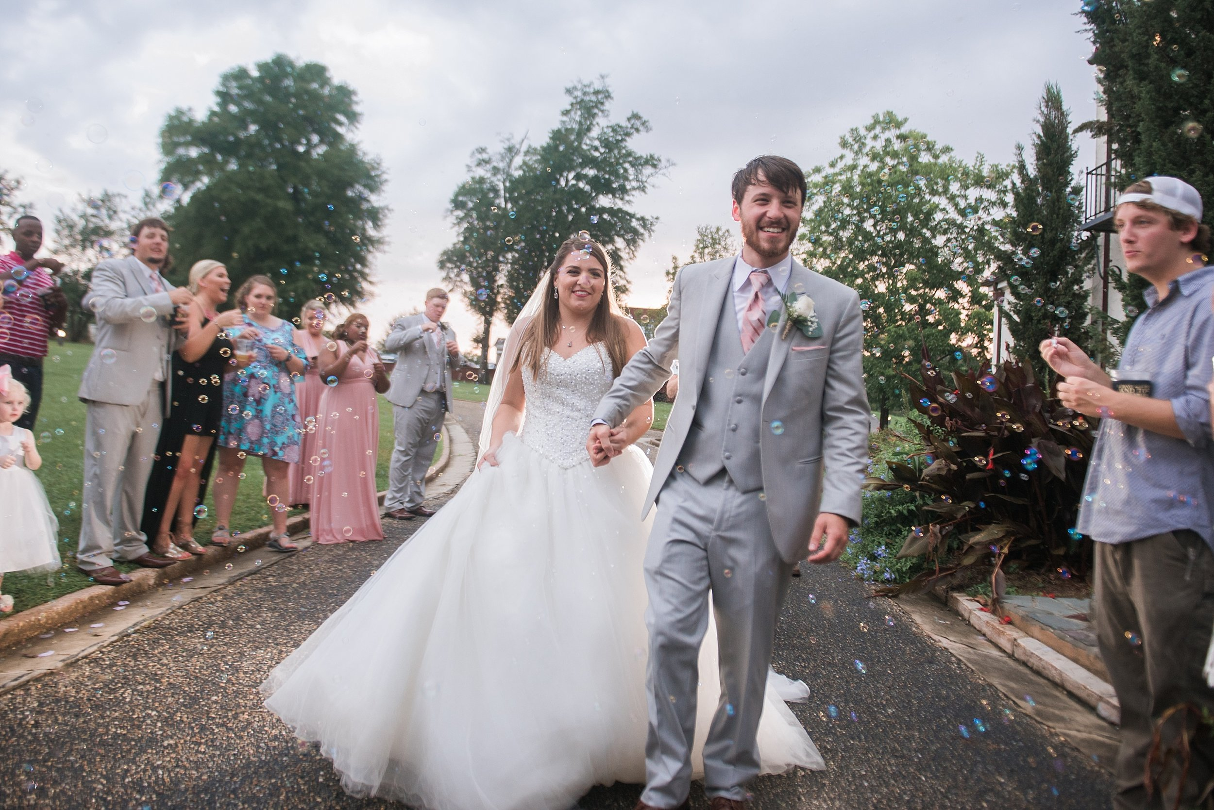 Bride and groom are showered with bubbles as they exit their reception