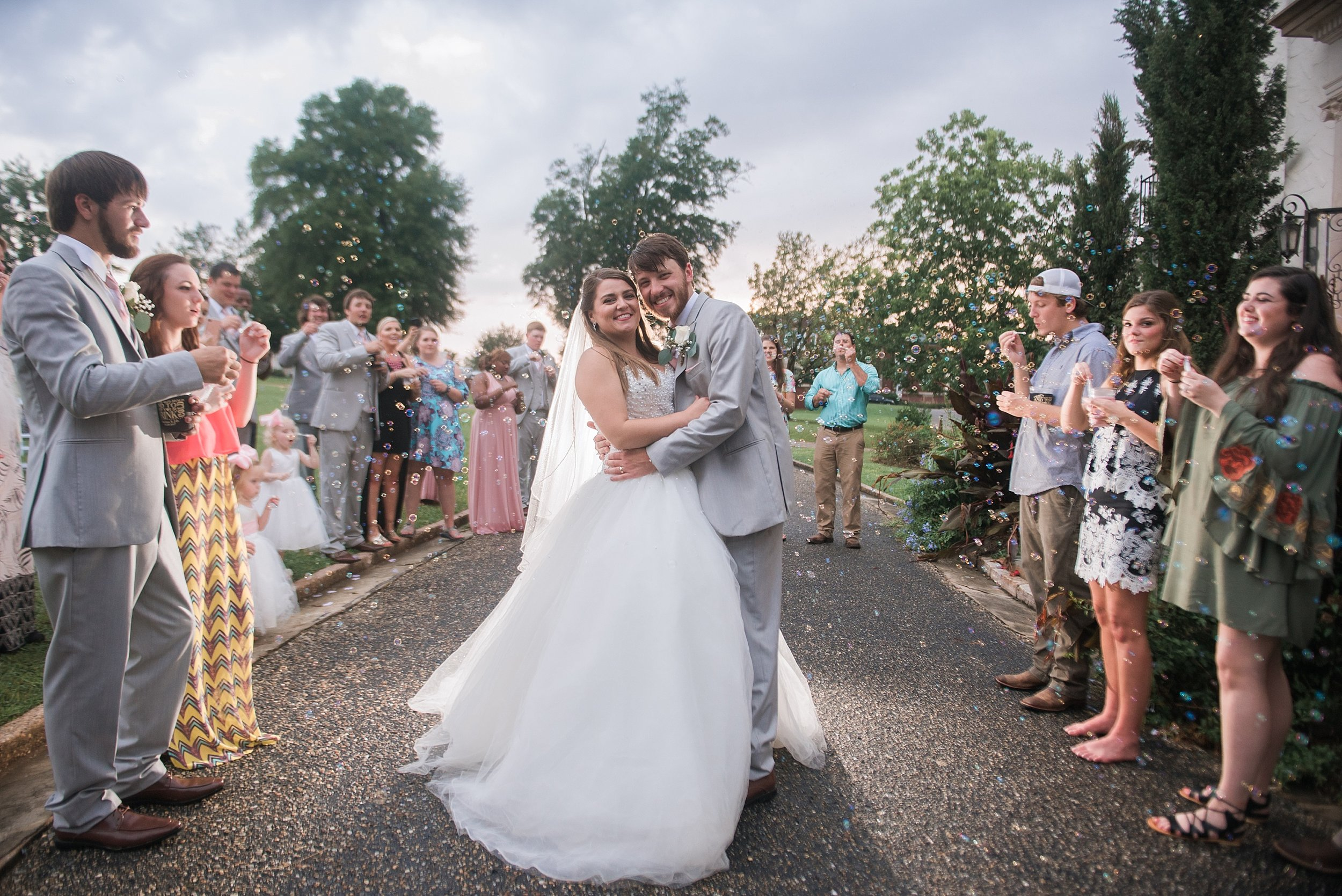 the newlyweds are showered with bubbles by their wedding guests as they leave their reception