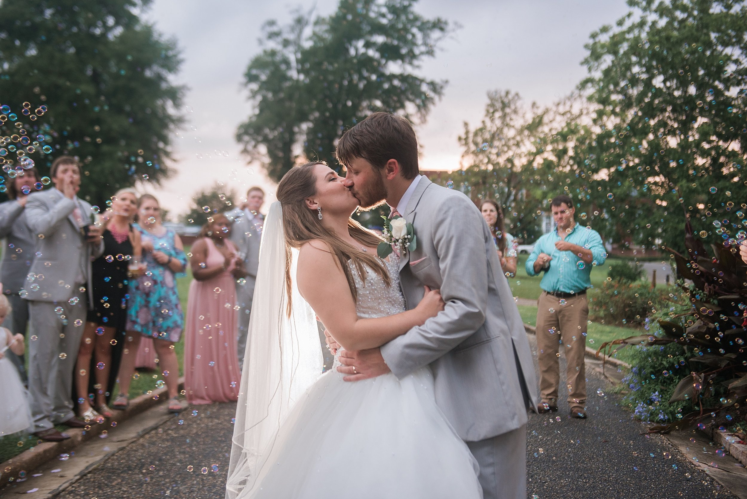 bride and groom kiss during their bubble wedding exit