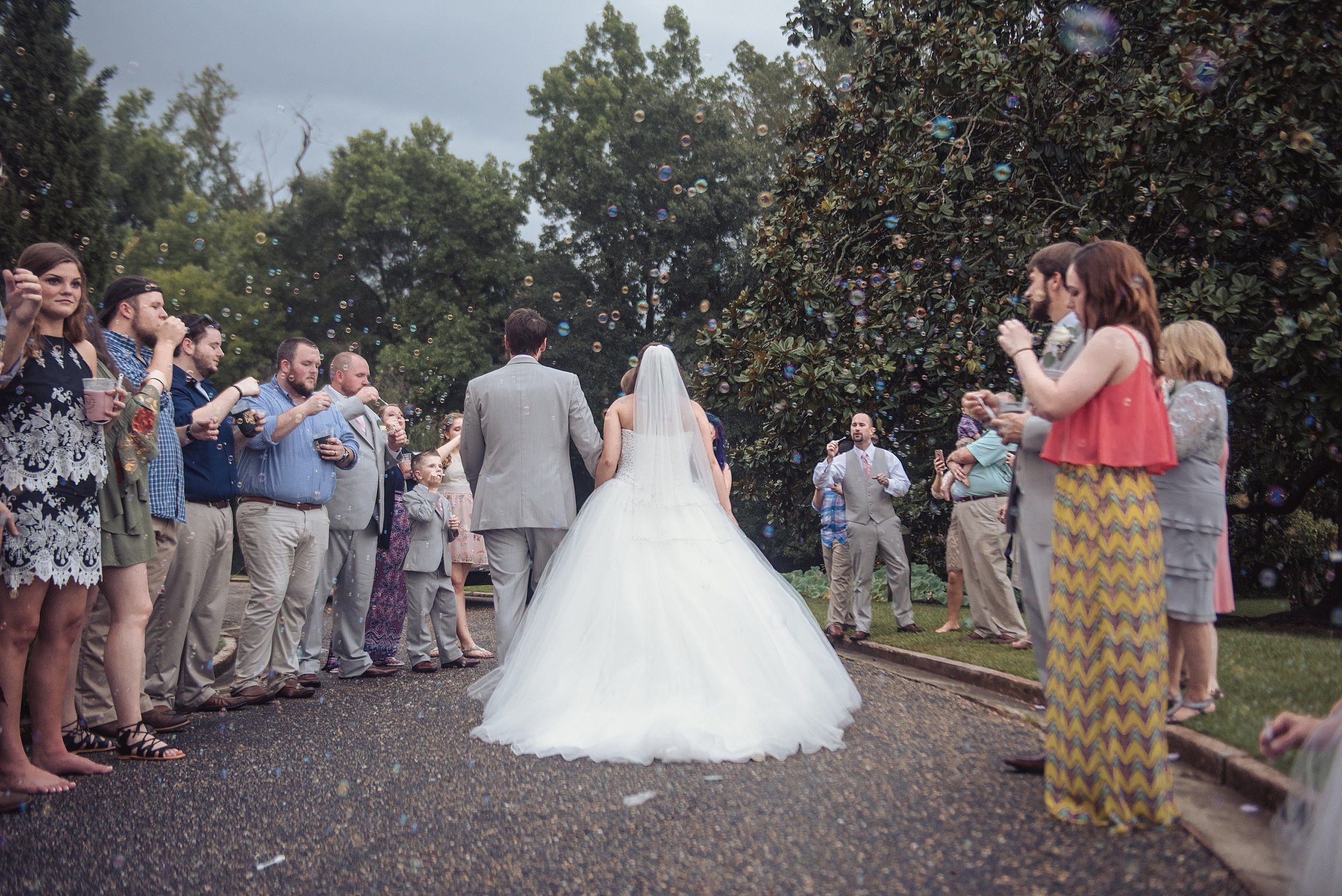 Bride and groom walk through bubbles as they exit their reception