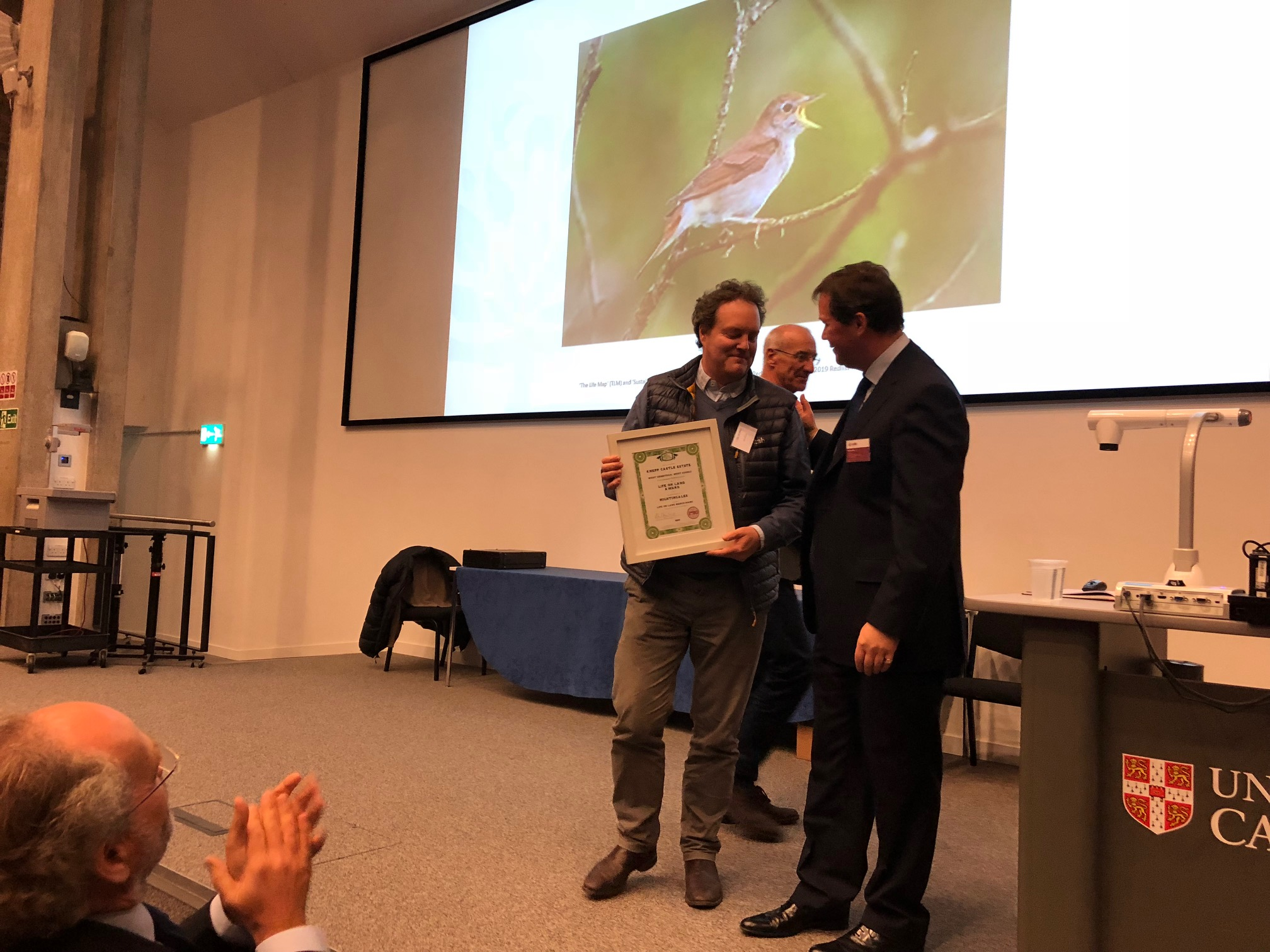 Jason collecting a prize from Cambridge University's CCI for Knepp's stunning nightingale recovery