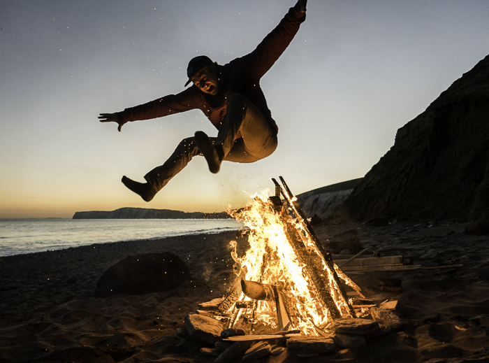 Hamish Smith leaping the fire on Compton beach