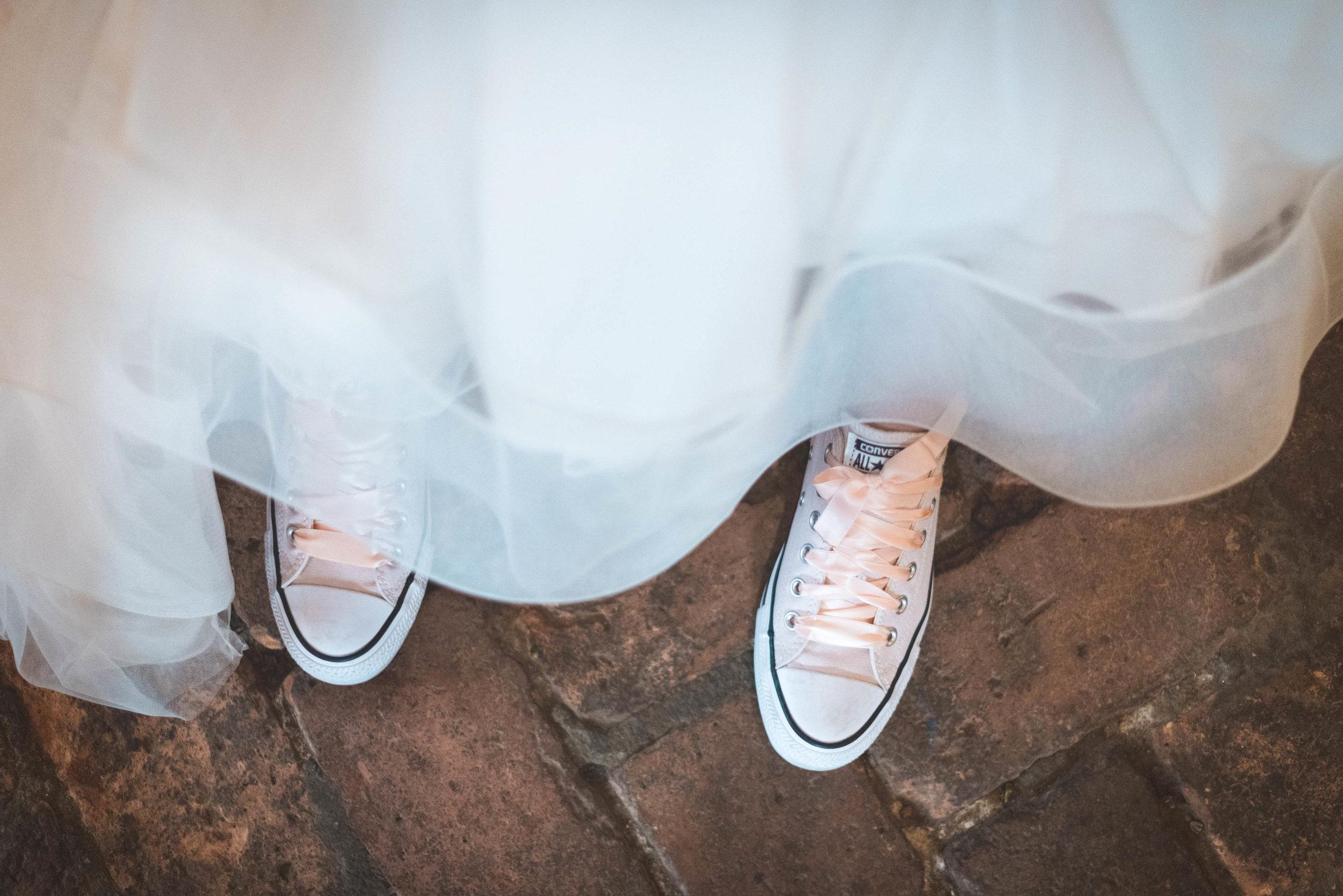 Deze bruid koos ervoor om haar bruidsjurk te combineren met leuke witte converse gympen. Deze leuke details maken jouw bruiloft zo speciaal en zijn dus belangrijk om terug te laten komen in de trouwreportage. Als trouwfotograaf let ik dus goed op dit soort details.