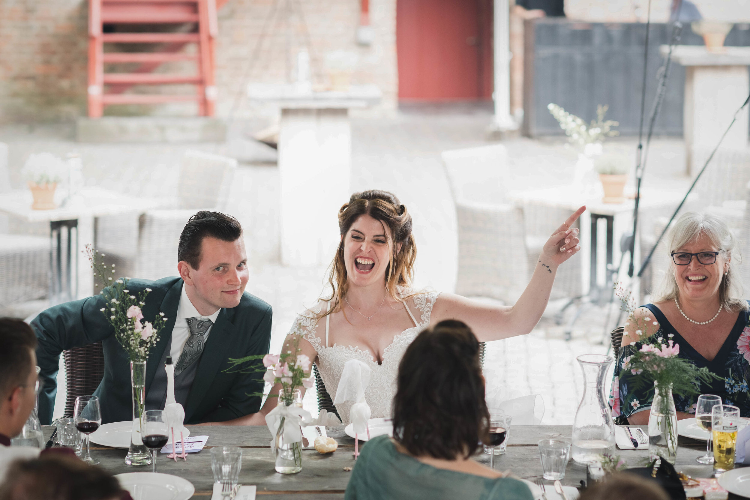 Een vrolijke bruid tijdens haar trouwdiner.