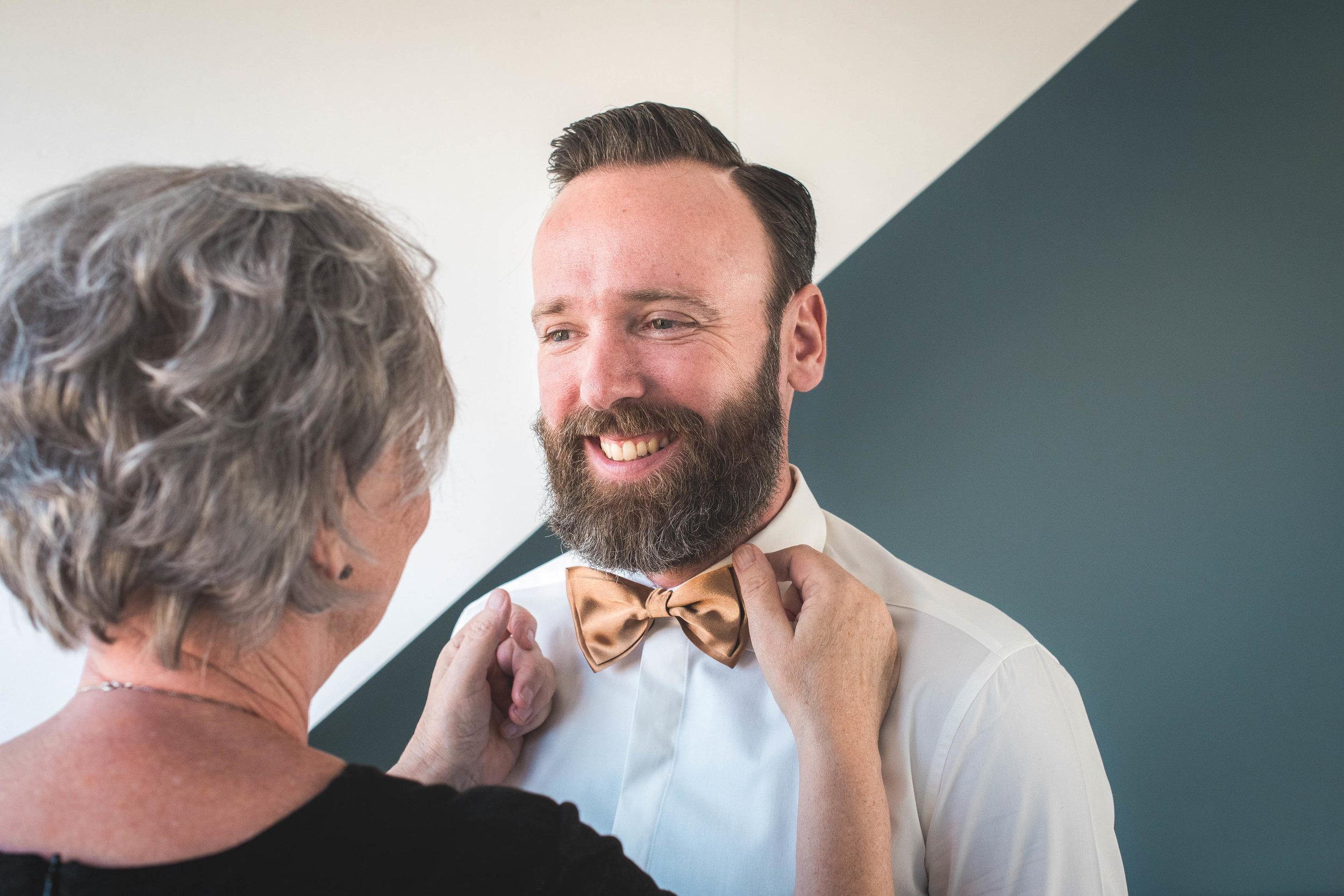 De moeder van de bruidegom doet het strikje van haar zoon goed. Op de ochtend van de bruiloft deden we een shoot op locatie tijdens het klaarmaken voor de grote dag.