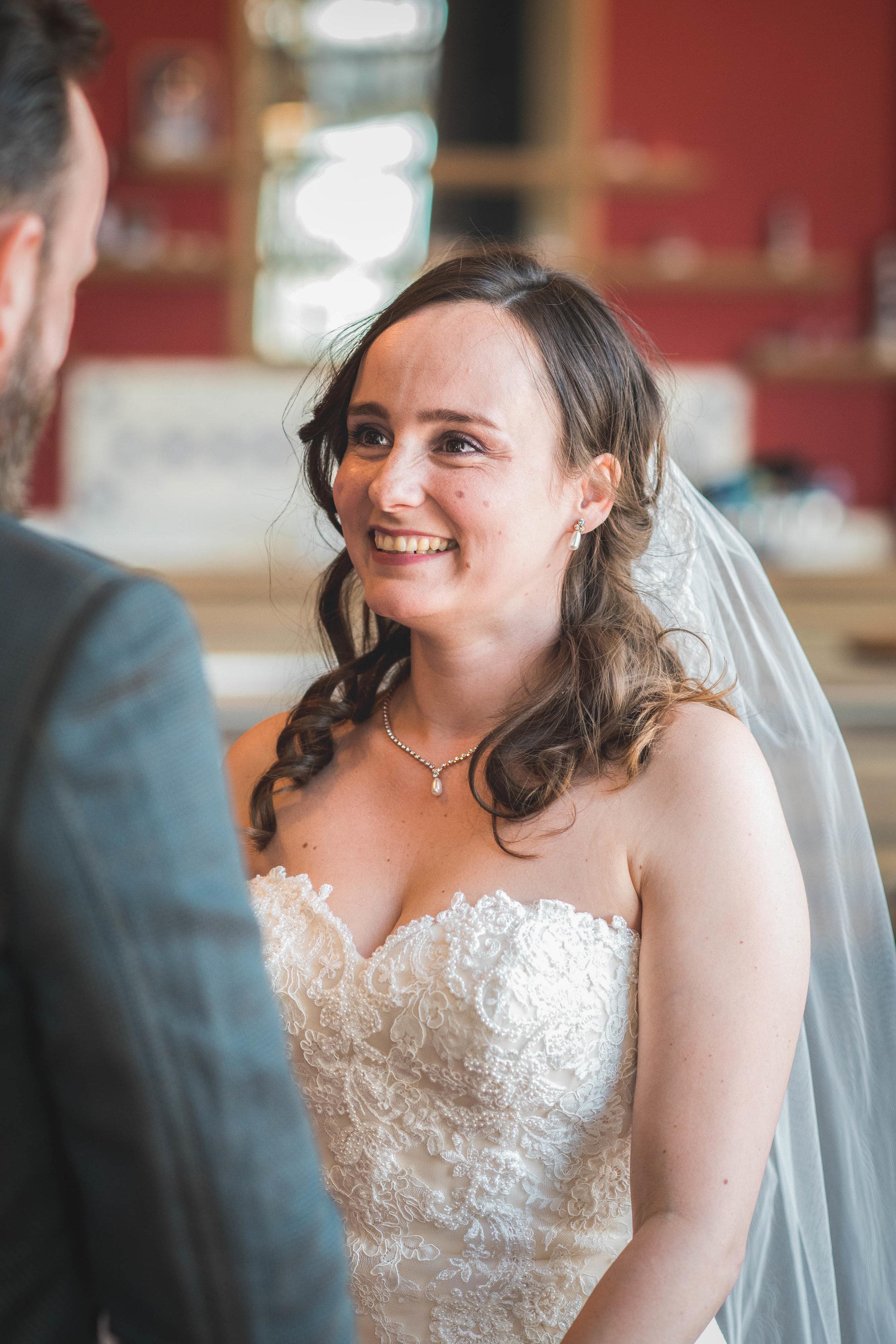Tijdens een trouwreportage probeer ik emoties te vangen op een ontspannen manier. Hier zie je de bruid lachen naar haar bruidegom tijdens de trouwceremonie in Rotterdam.