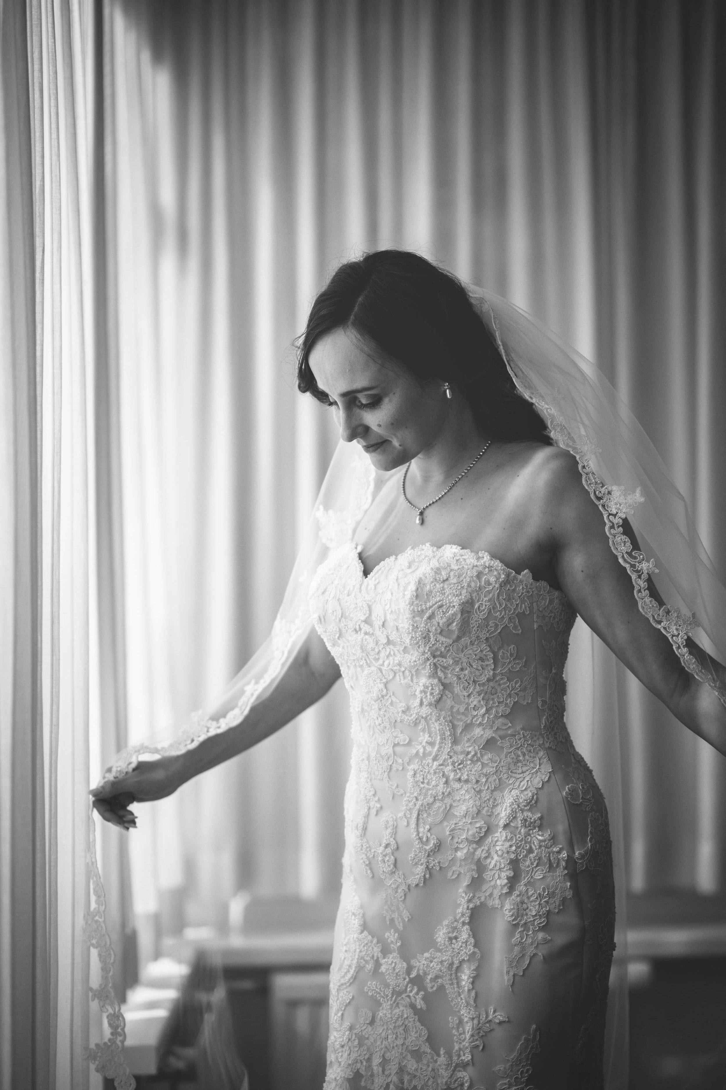 Een foto van de bruid in haar bruidsjurk nadat ze net klaar is met zichzelf klaarmaken voor de bruiloft.
