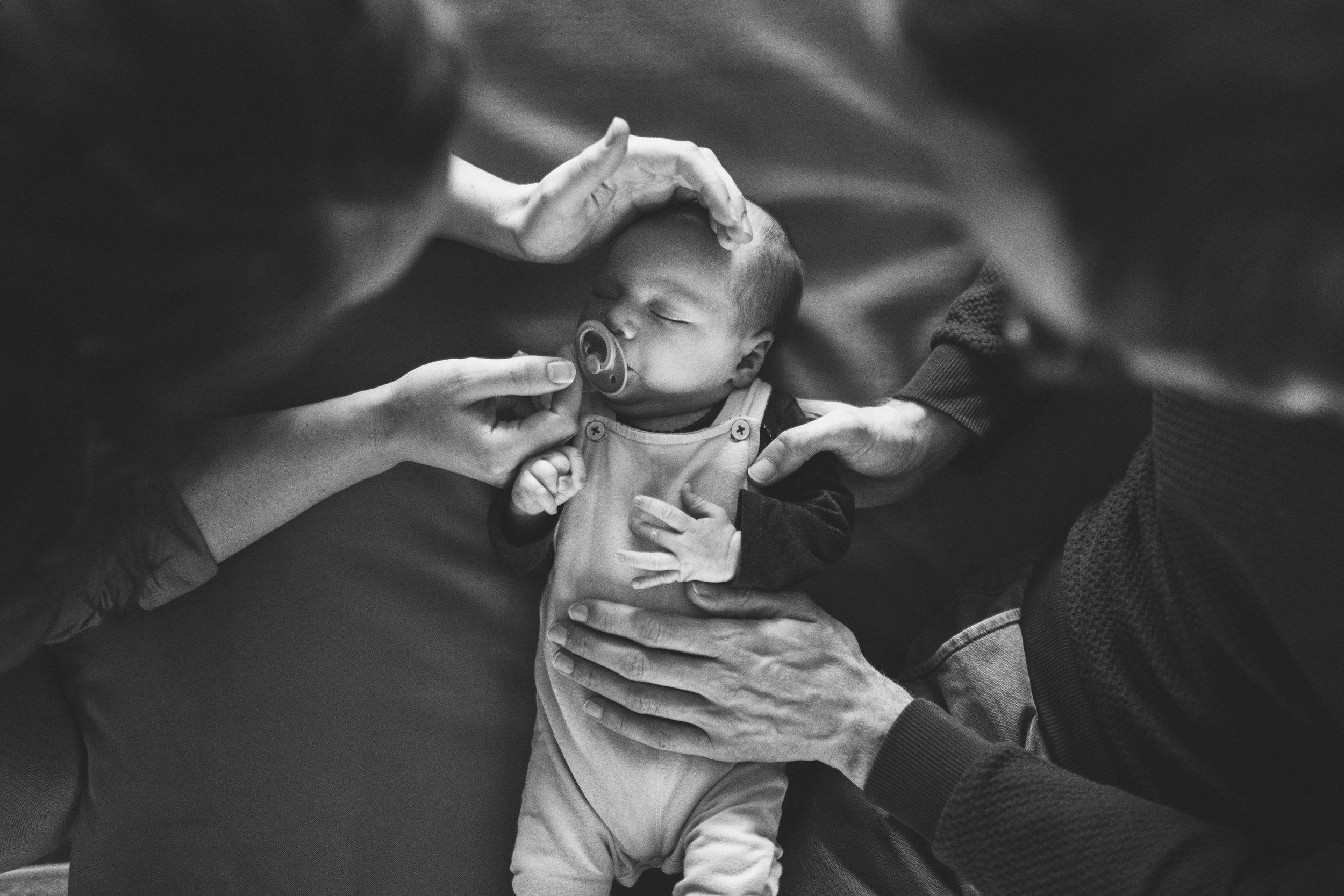 Een zwartwit foto van een pasgeboren baby tijdens een babyshoot. Deze babyfoto is van bovenaf genomen.
