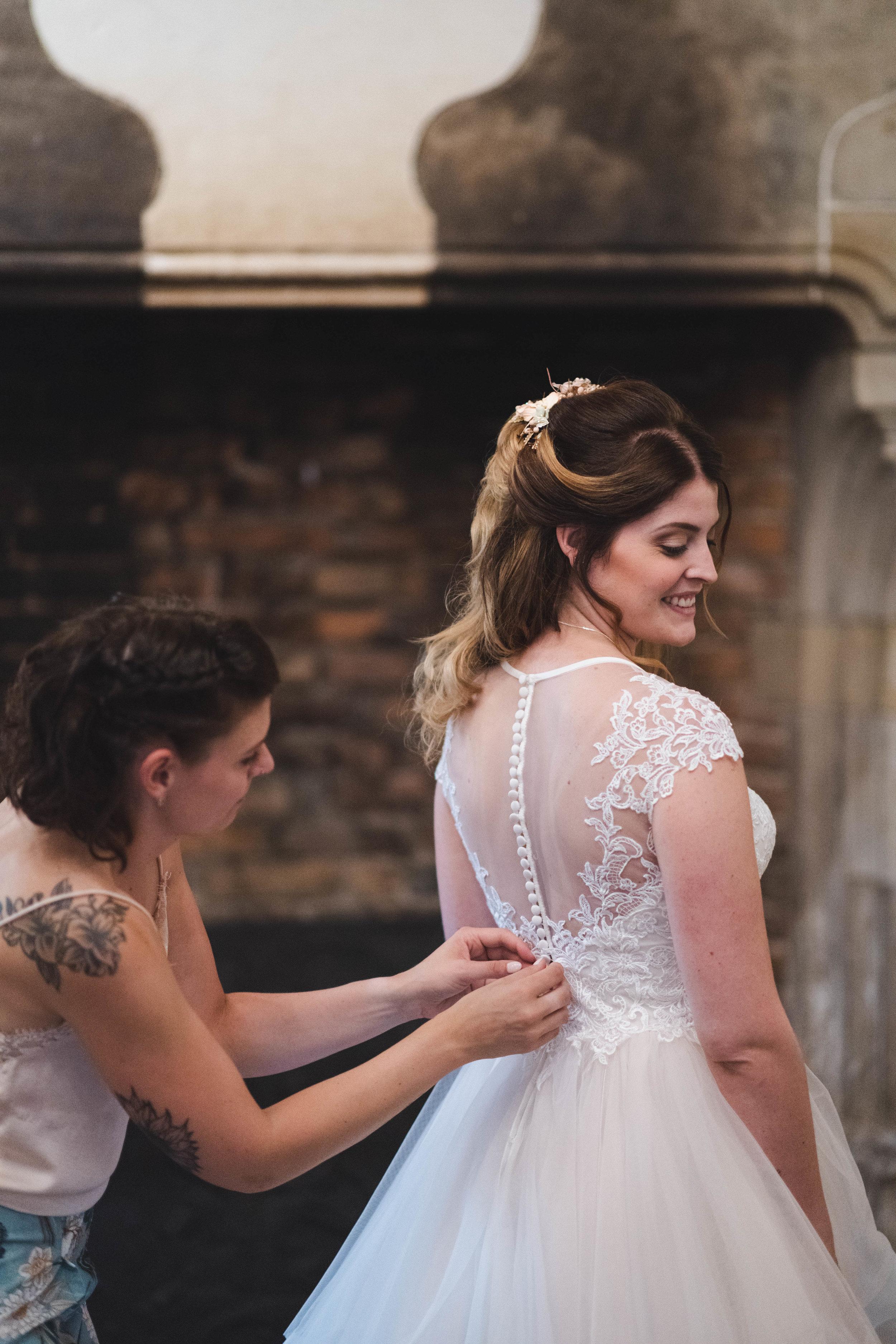 De zus van de bruid helpt haar in haar bruidsjurk. Deze bruiloft vond plaats in Kasteel Duurstede. Ik ben als trouwfotograaf meer dan bereid om mee te gaan naar allerlei locaties in Nederland.