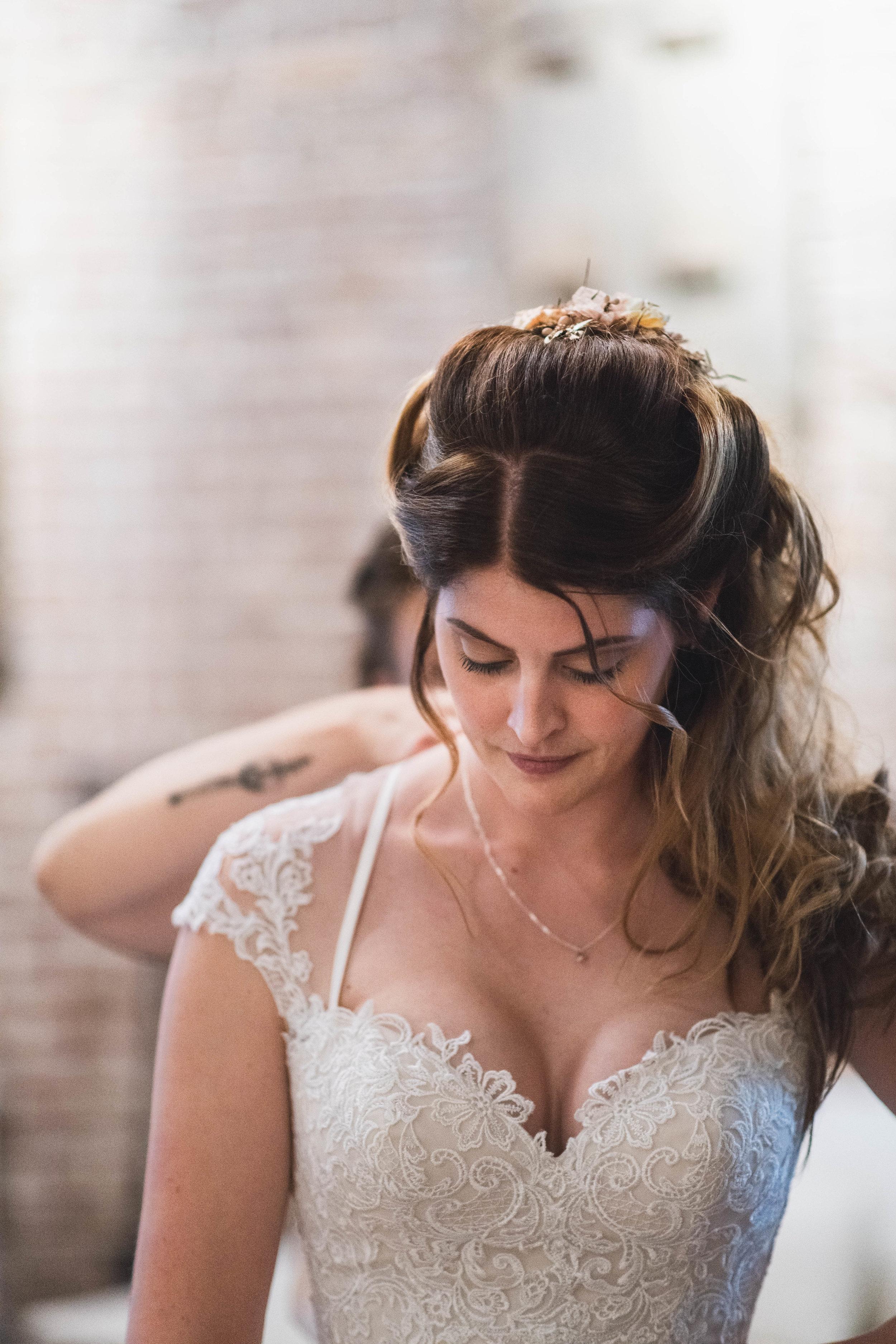 De bruid wordt in haar jurk geholpen op haar bruiloft.