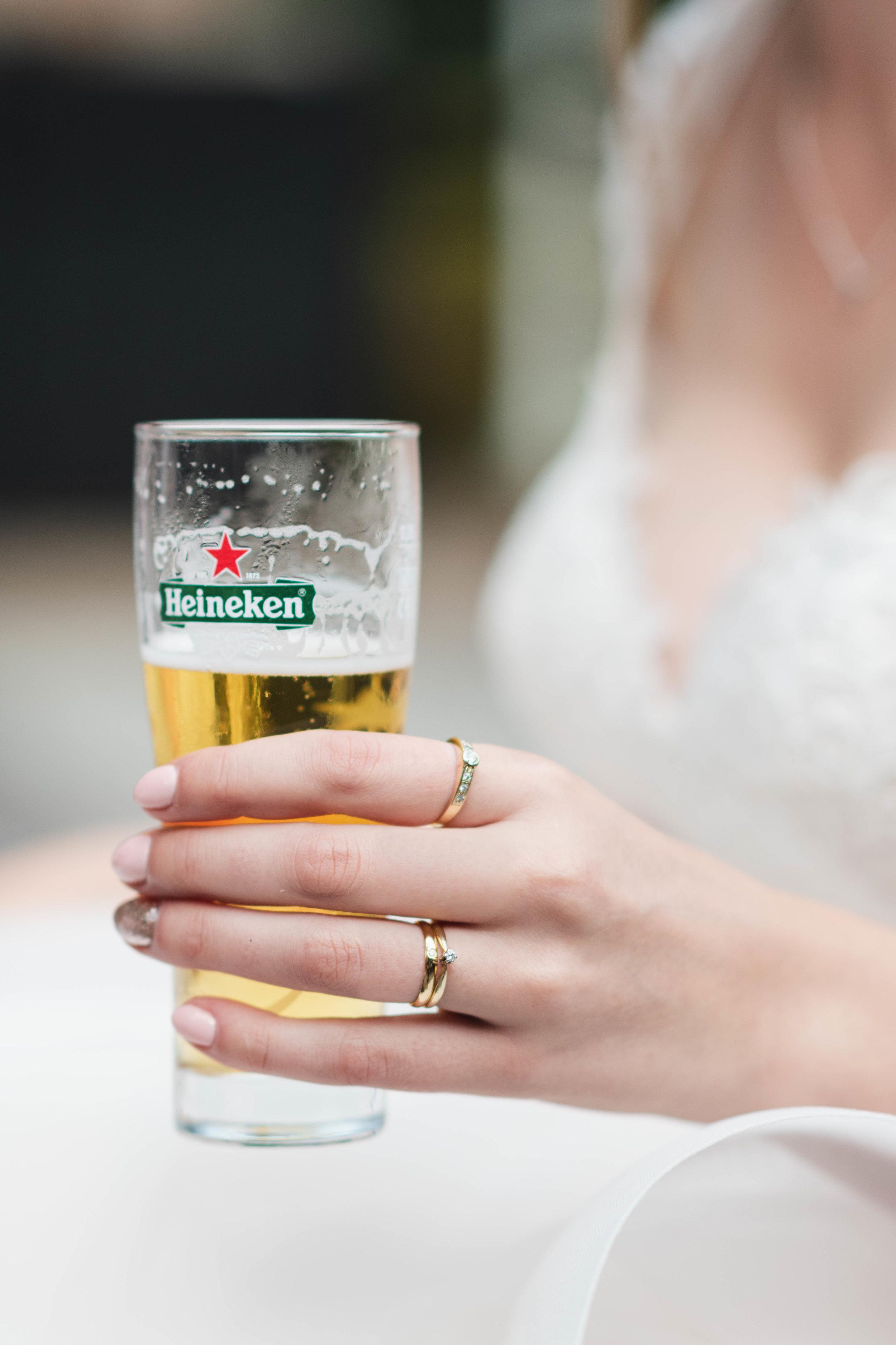 De bruid drinkt lekker een biertje terwijl ze haar nieuwe trouwring showt.