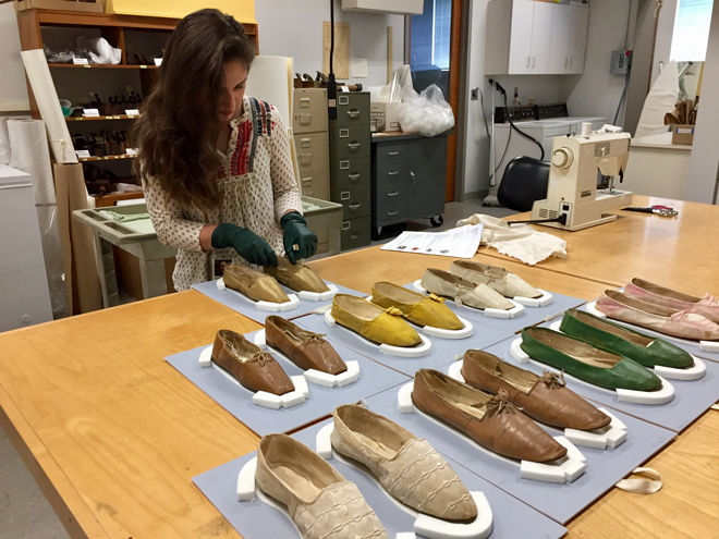 Figure 1. Danielle adding the finishing touches to the mylar quarter inserts for a pair of gold silk slippers with cotton lining and leather soles [1]. These shoes were likely worn by Clarissa Dwight on her wedding day in 1842 in South Hadley, MA. Also pictured (L to R) are slippers in brown leather [2], yellow silk [3], and white leather [4]. In the foreground are slippers in (L to R) white silk [5], brown leather [6], green leather [7], and pink leather [8].