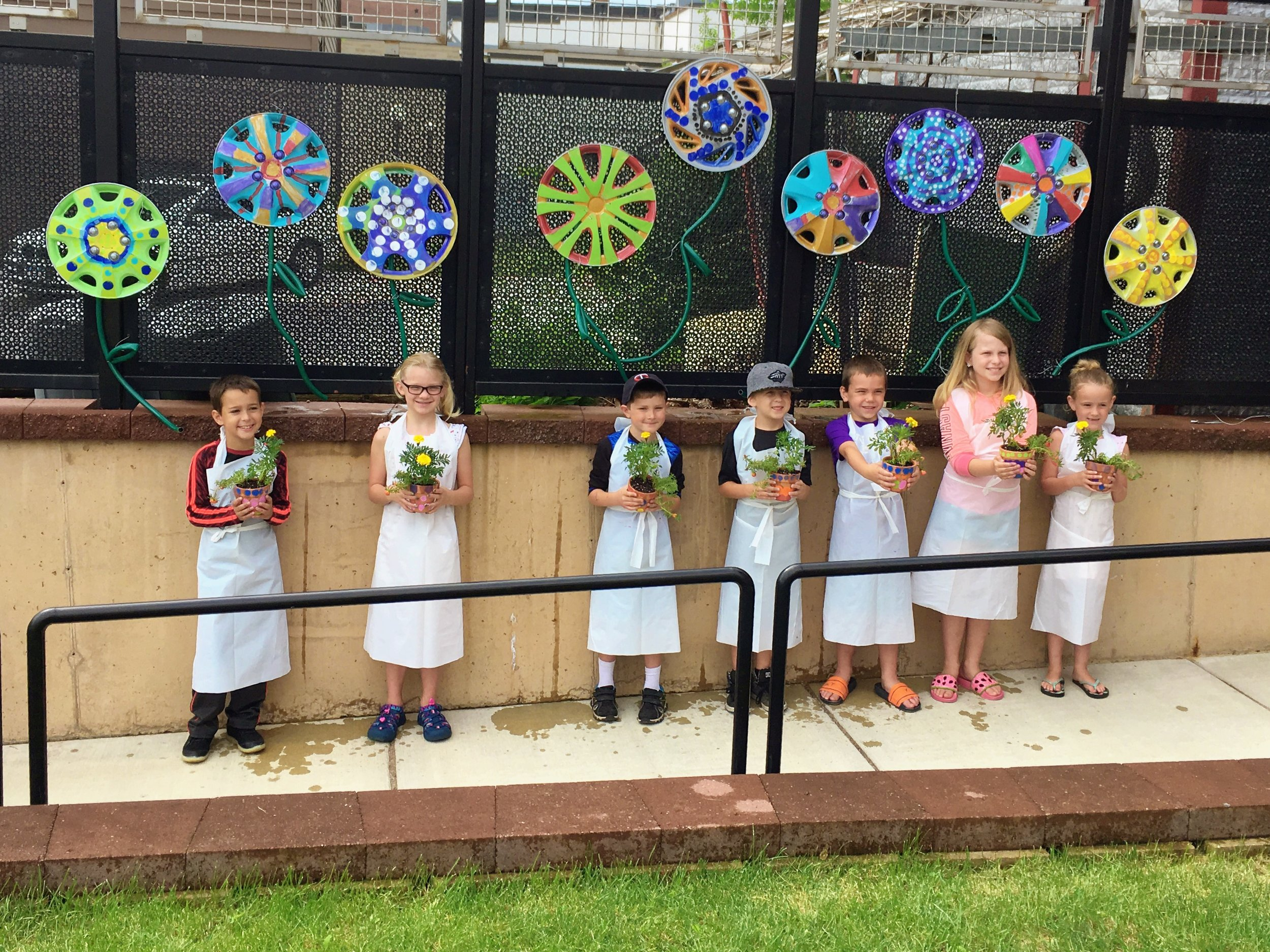 Creativity Camp participants with their hubcap flowers along the fence in The Grand's backyard.