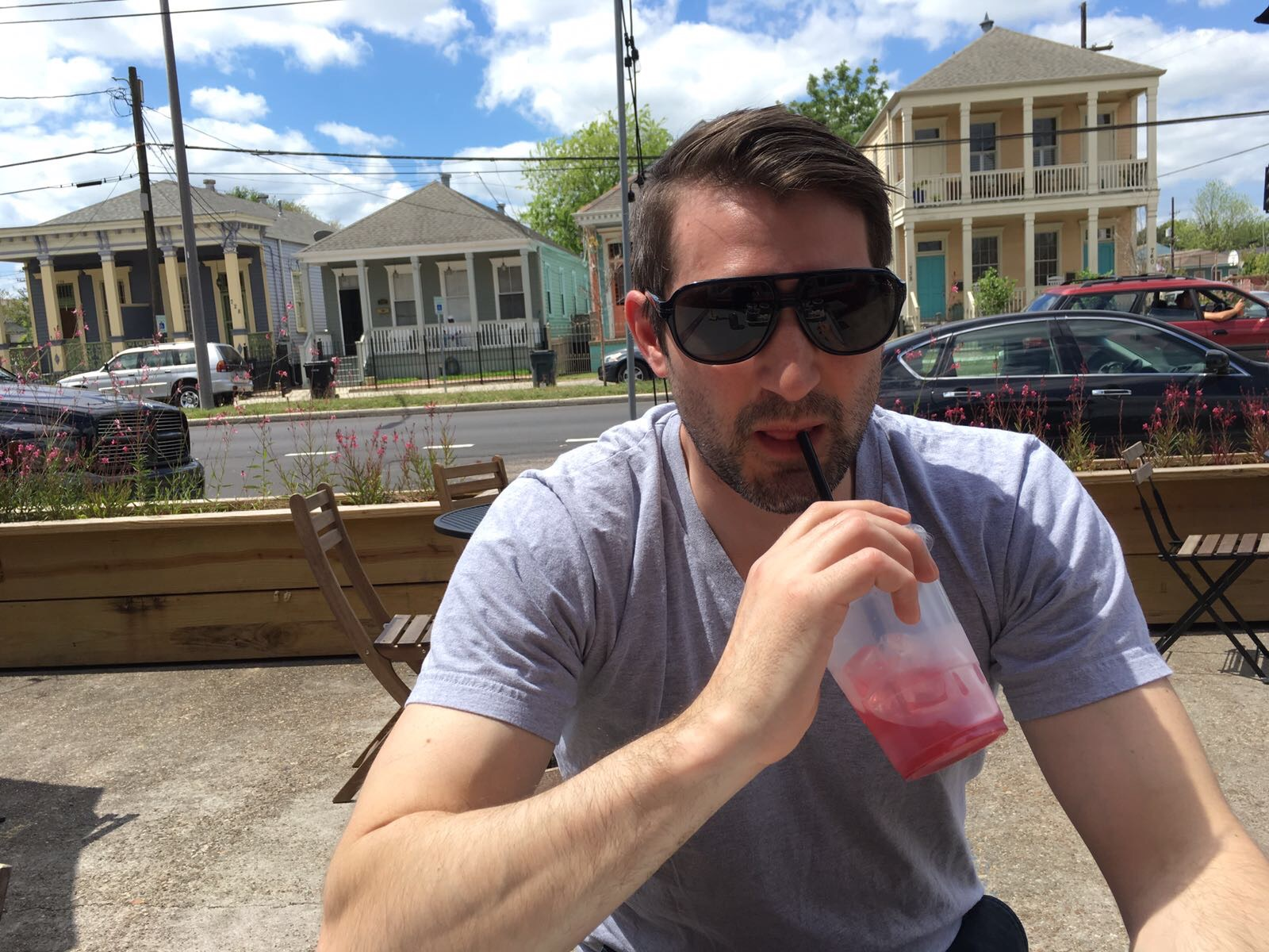 """Jimbo slurping a """"to-go"""" cocktail (a NOLA perk) at Turkey and the Wolf. That two story house behind him is our Air B&B."""