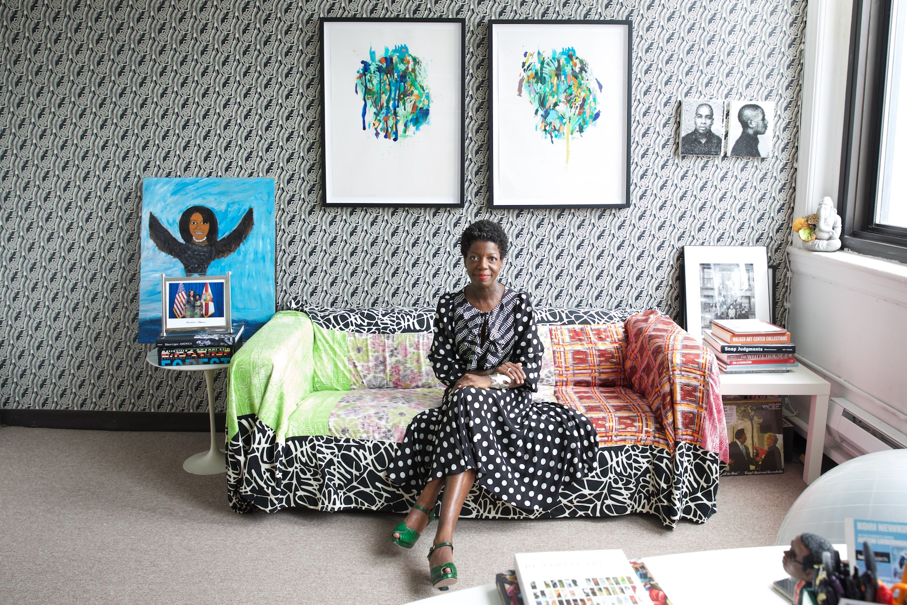 Thelma Golden, in her cool office, wearing cool clothes, surrounded by cool books and cool art ( Via Artsy )