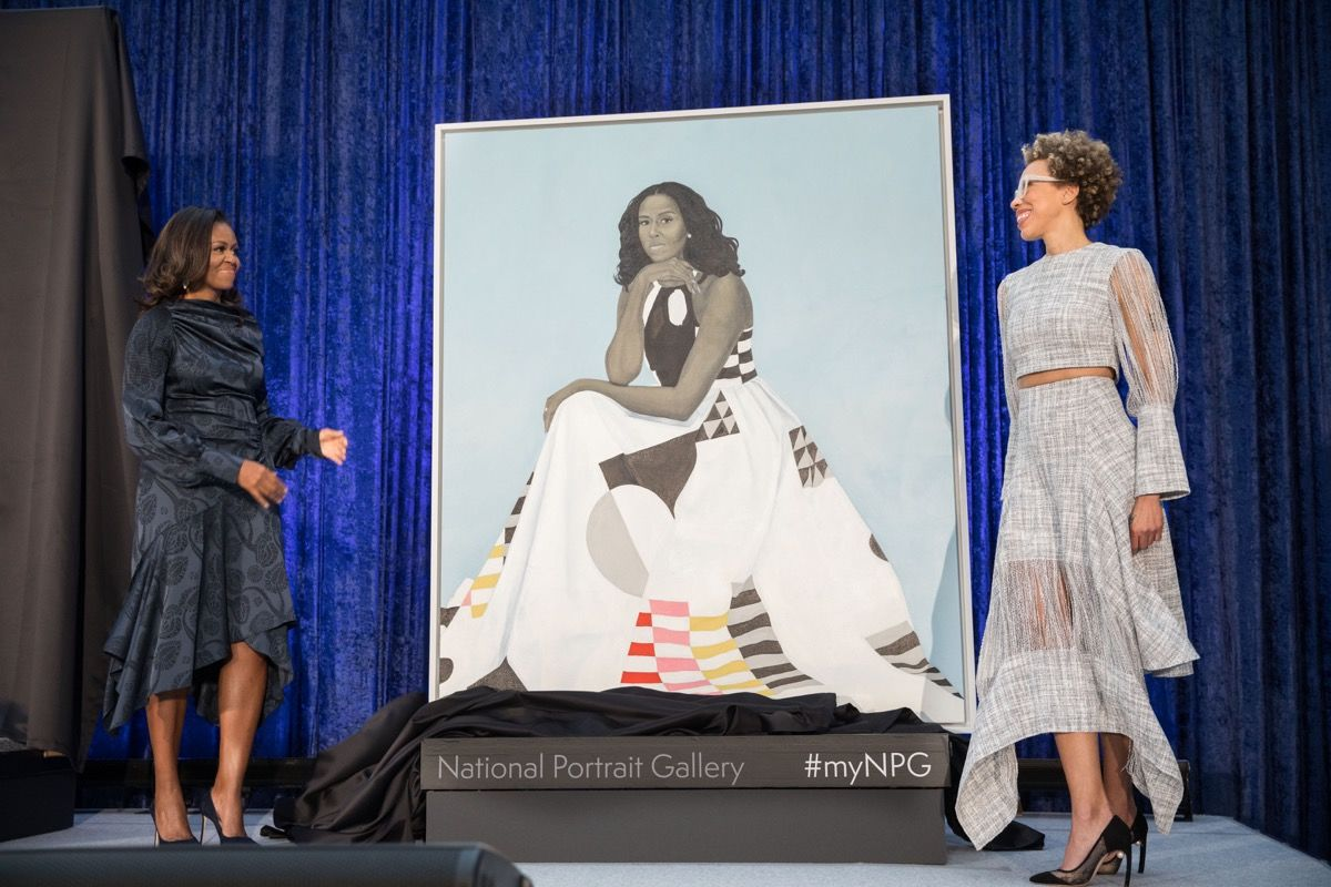 Amy Sherald (right) with the portrait of MIchelle Obama and Obama herself at the unveiling in 2018- via  Artsy