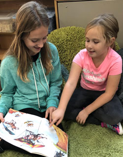 Keira finds a comfortable spot to read with her Grandville penpal