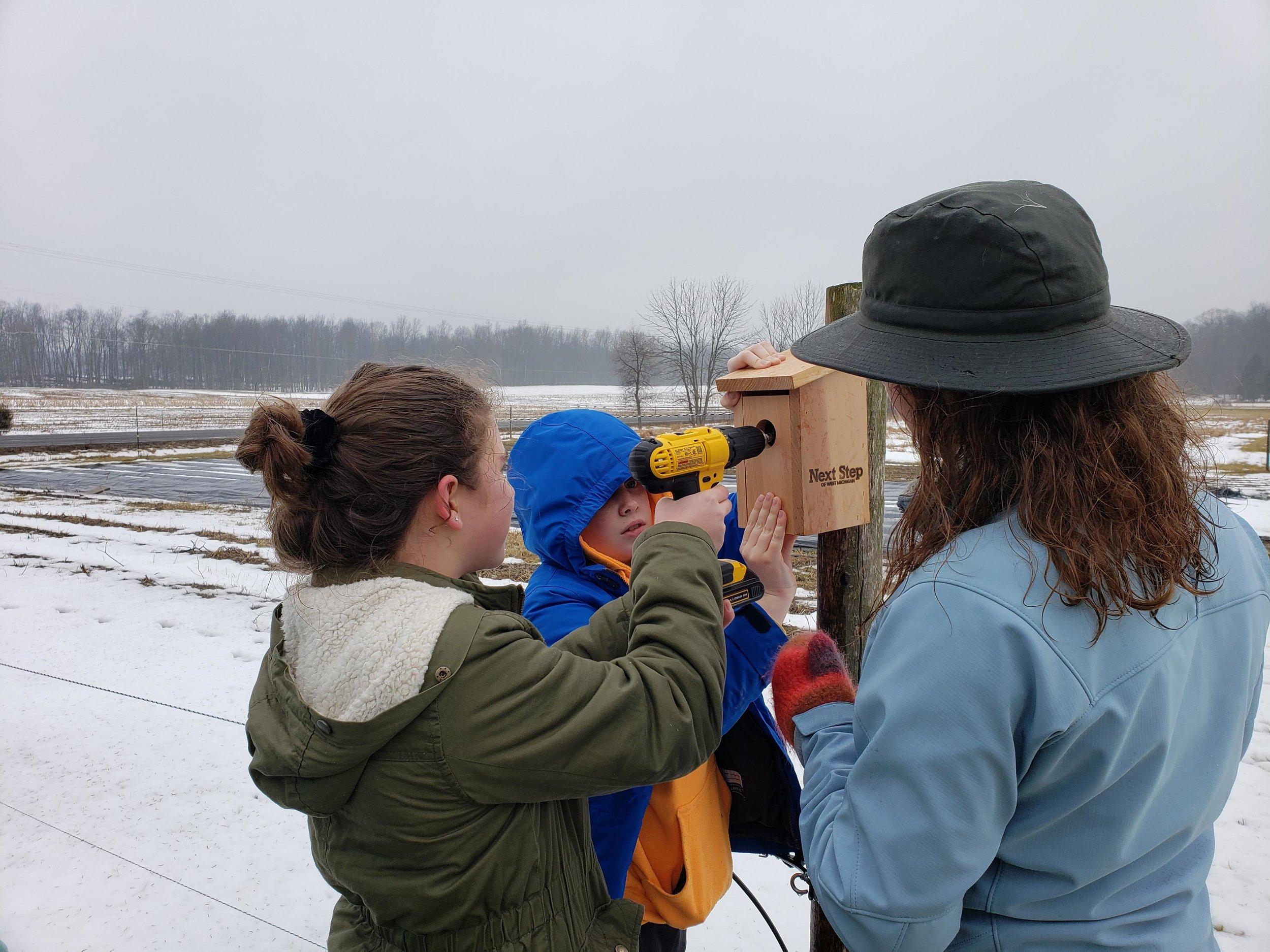 Students install birdhouses to promote native habitat