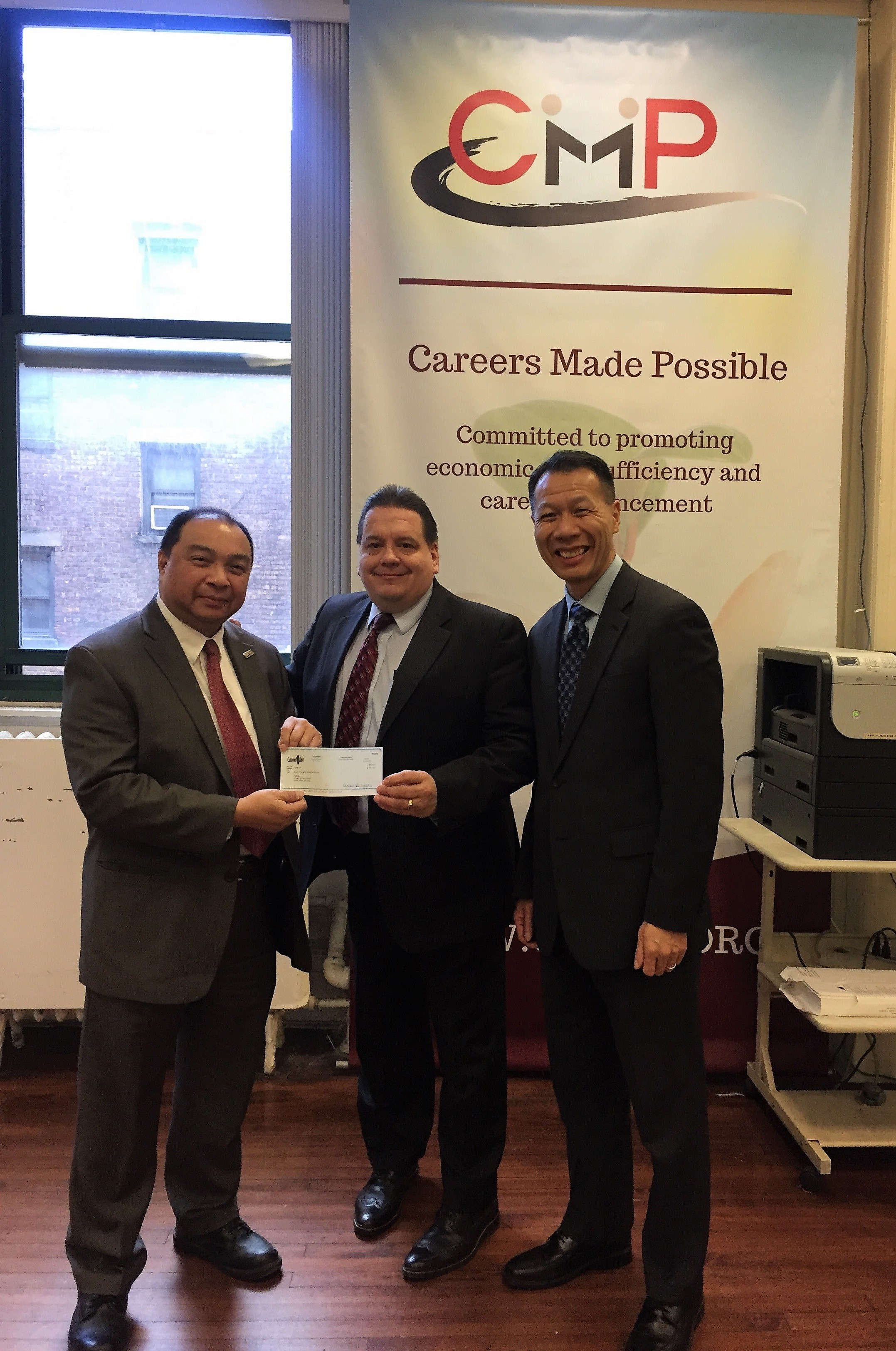 Customers Bank Senior Vice President  Mr. Paul Hodowanec  (center) and Vice President  Mr. Danny Wong  (right) handing over the donation check to CMP Executive Director  Mr. Hong Shing Lee  (left)