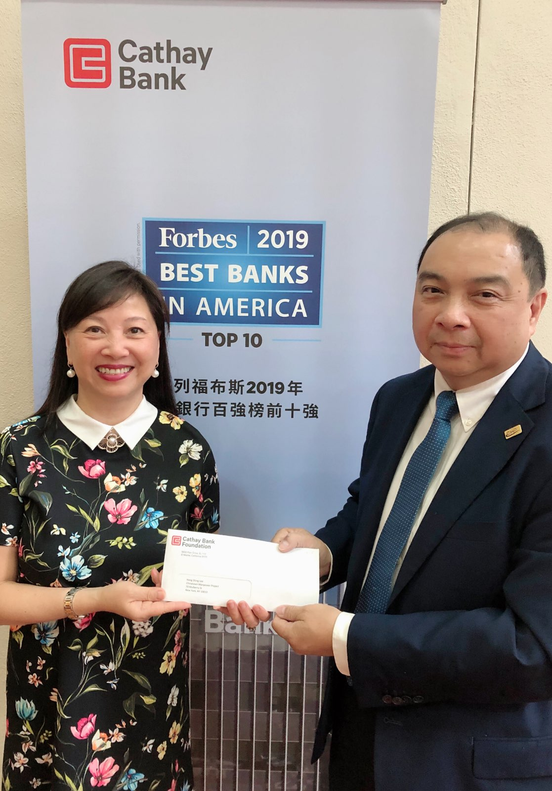 Cathay Bank Senior Vice President  Ms. Elizabeth Lee  (left) is handing over the donation check to CMP Executive Director  Mr. Hong Shing Lee  (right)