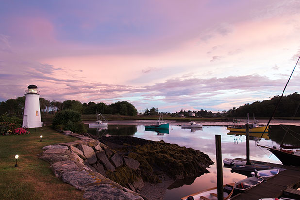 An image of a lighthouse at sunset, shot at Nonantum resort on the coast of Maine.