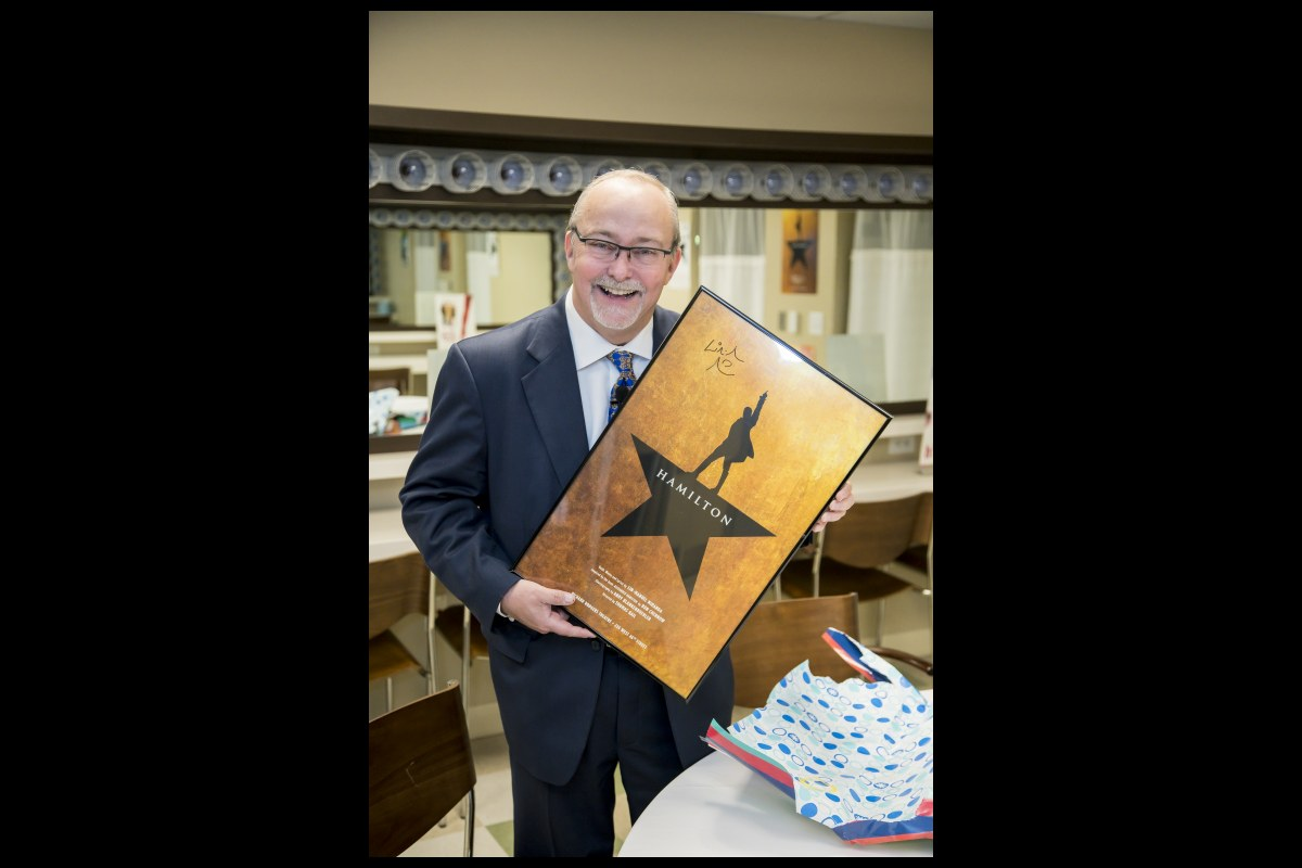 """Myron Martin, president and CEO of the Smith Center, with a """"Hamilton"""" poster signed by Lyn-Manuel Miranda. Photo: Jerry Metellus"""
