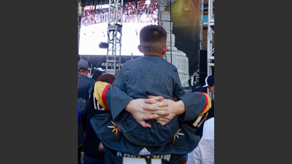 OH, THE STRESS: A FATHER HOLDS HIS SON IN THE TENSE, WANING MOMENTS OF GAME 5. Photo: Norm Clarke