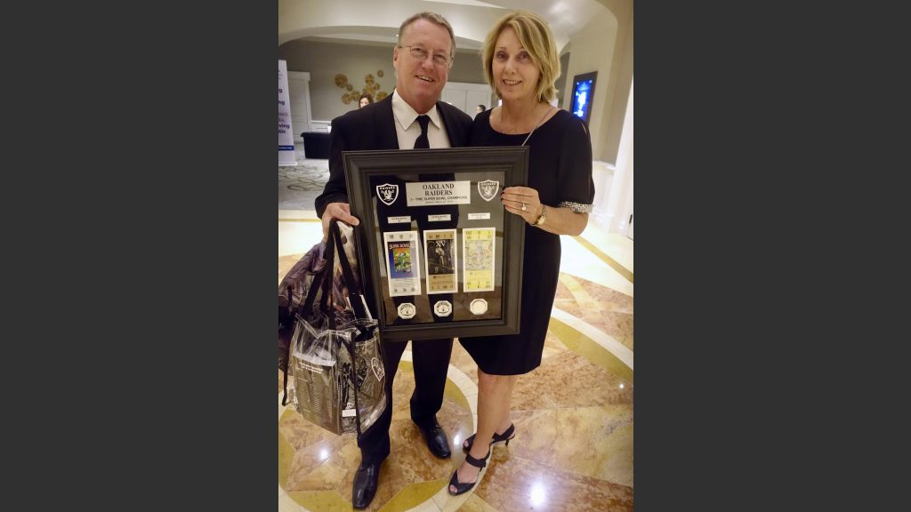 Chris and Di Wolfgram of Windermere Real Estate with Raiders memorabilia and a trip to Indianapolis for a game this fall.
