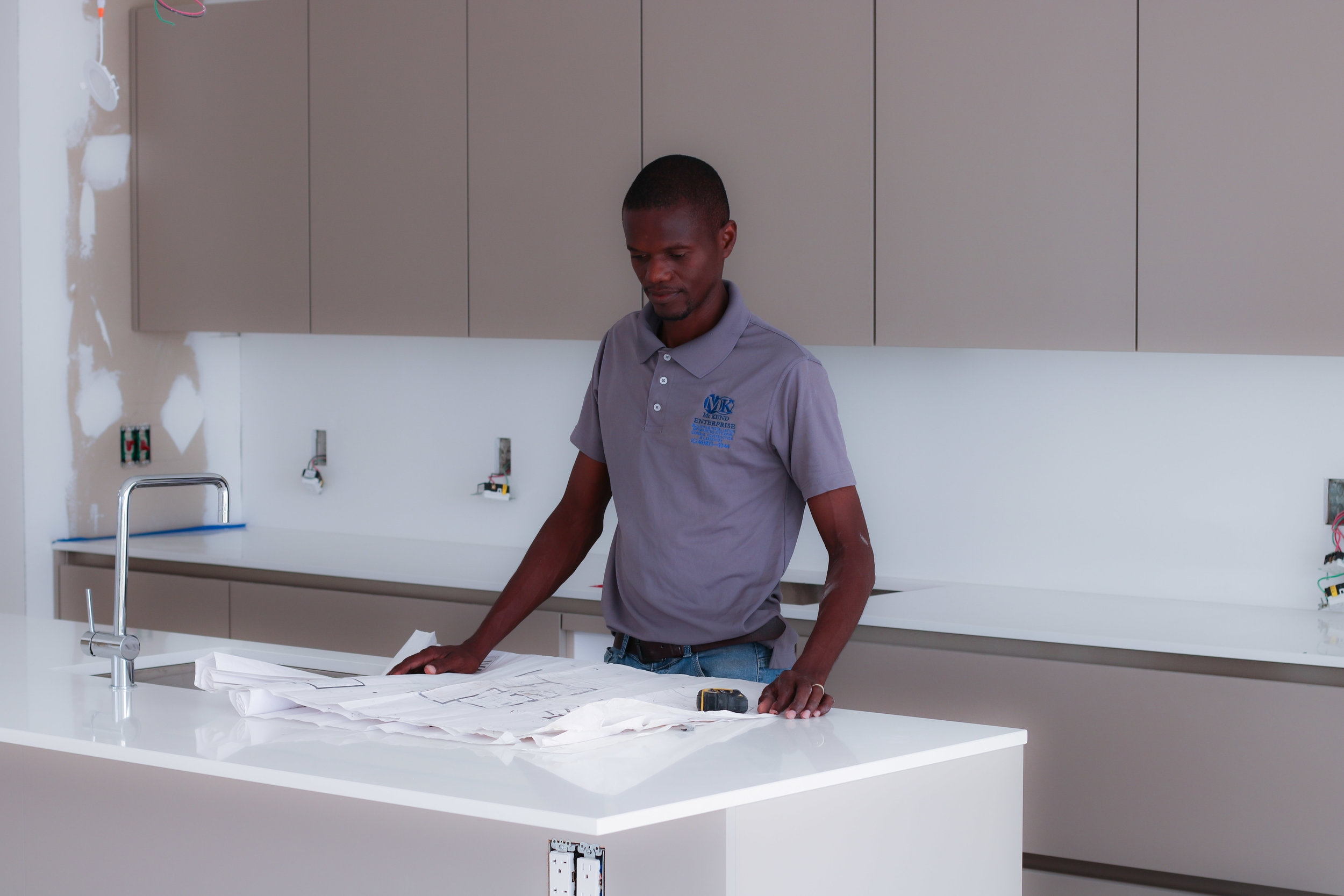 Seon examines the plans for one of his kitchen installations.