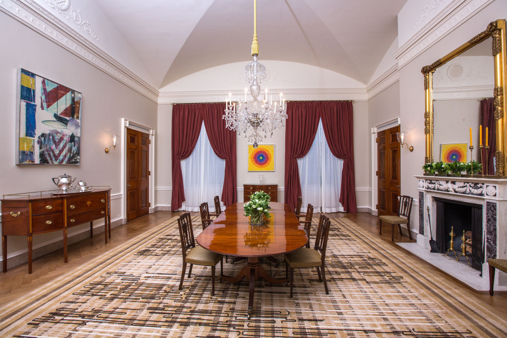 Dining room during the Obama administration. Alma Thomas' artwork  Resurrection  adorns the far wall while Robert Rauschenberg's  Early Bloomer [Anagram (A Pun)]  hangs above the buffet to the left.