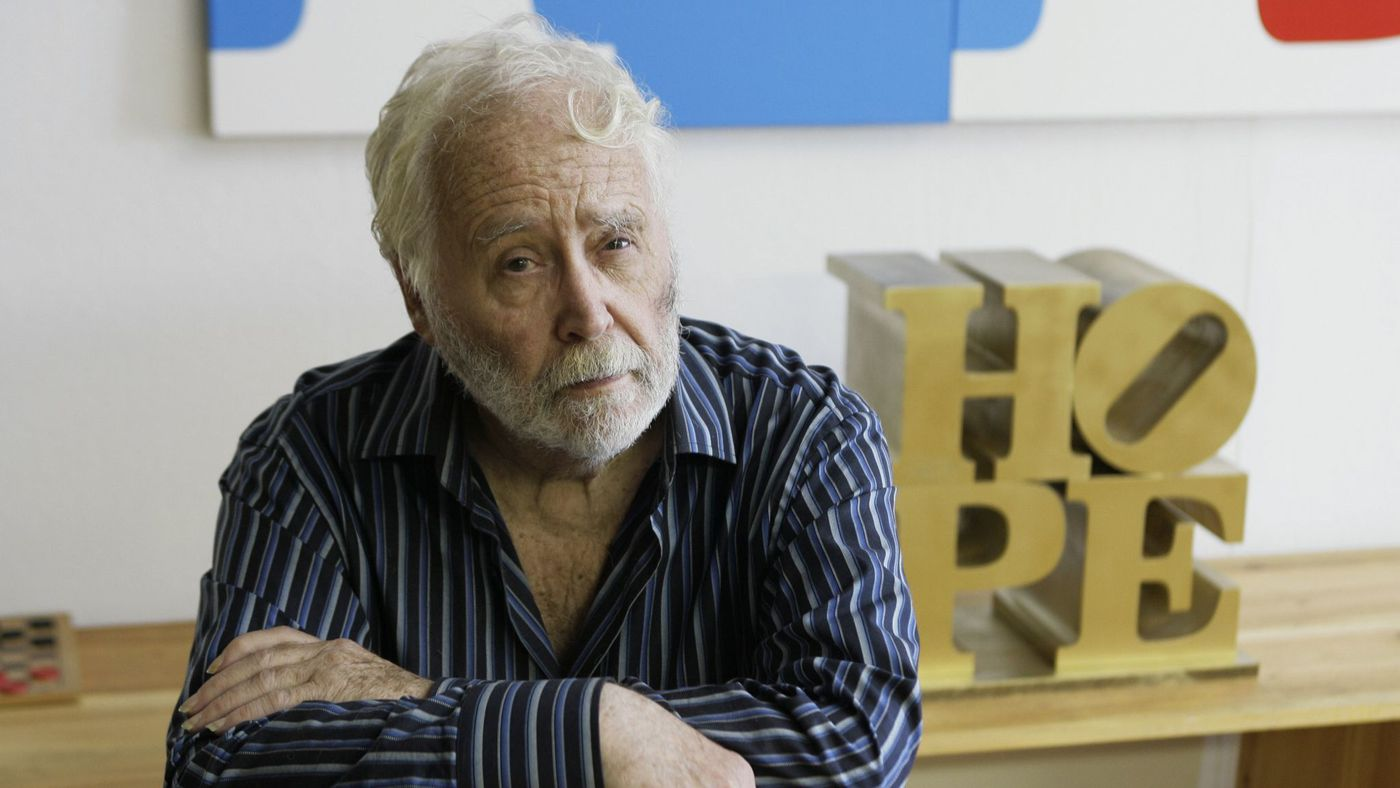 Robert Indiana with a small scale version of his sculpture  Hope