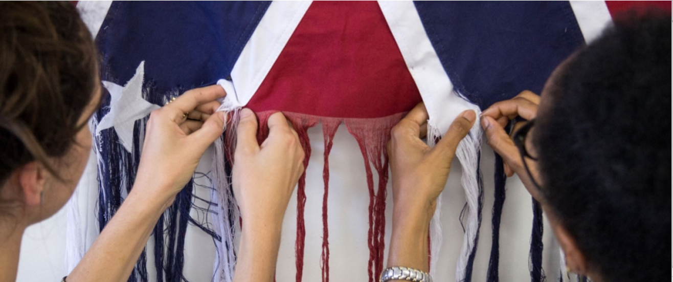 Sonya Clark and a visitor unpicking the flag.  Unraveling , Sonya Clark, 2015, Cotton Confederate Flag. Photo: Courtesy The Artist. Photo Taylor Dabney