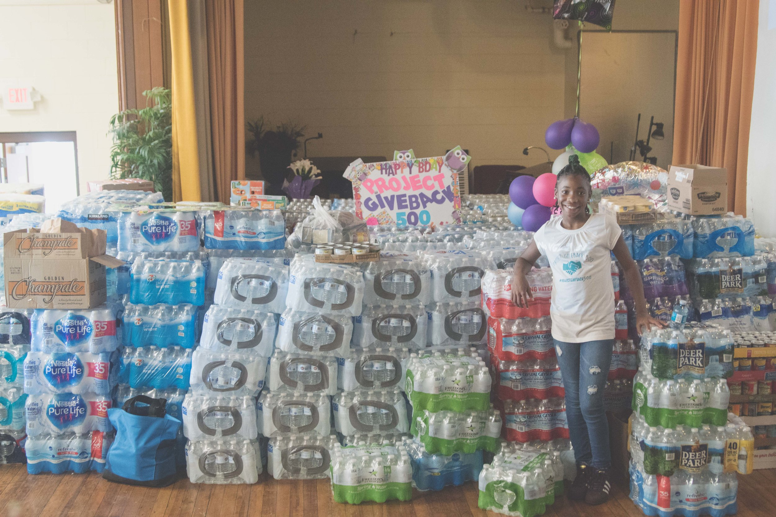 12 year-old DaShai Morton standing in North Forestiville Elementary School with over 500 cases of water she collected in donations for Hurricane Irma and Hurricane Maria victims in Puerto Rico.