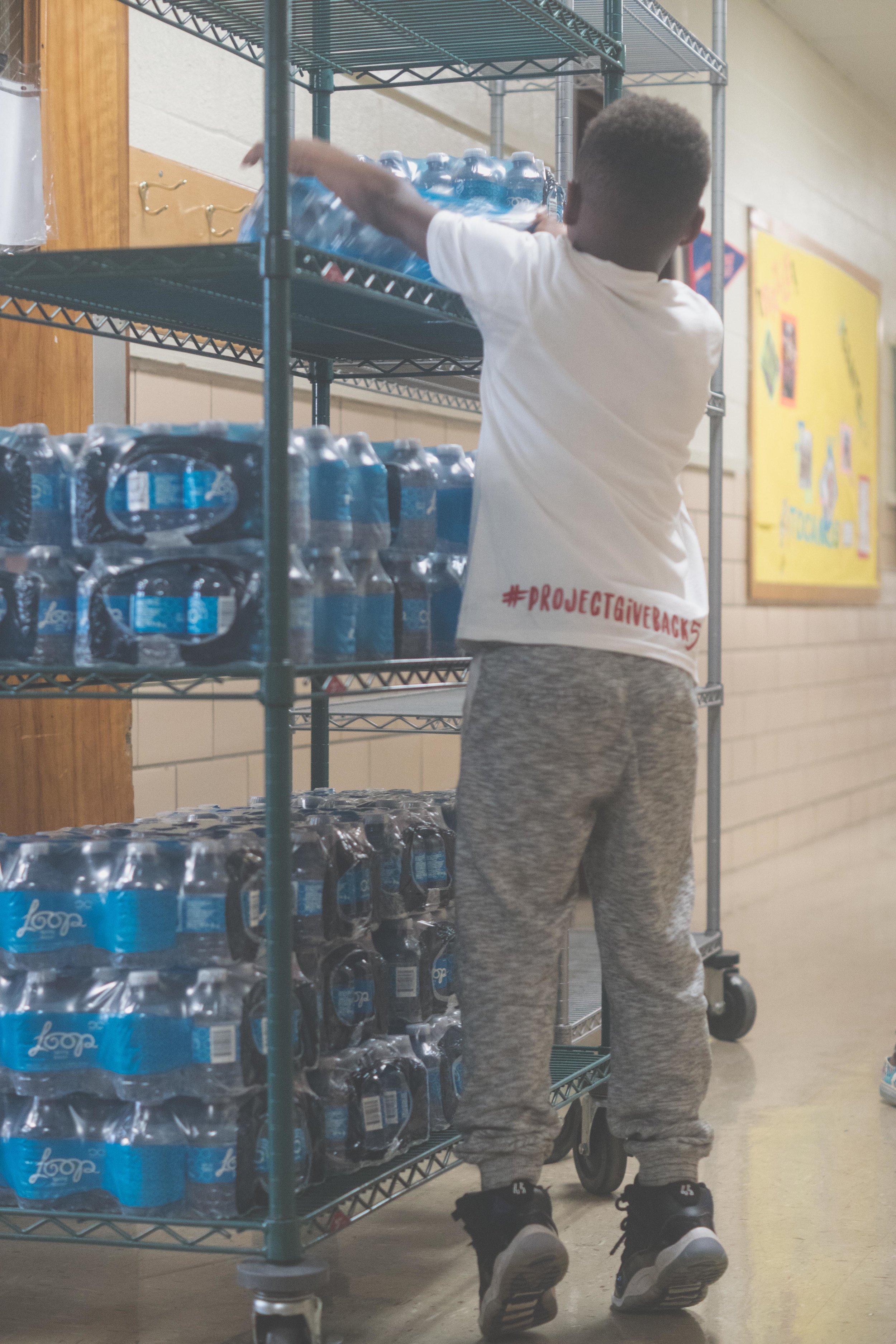 Forestville student helps DaShai Morton pack water donations for Hurricane Irma and Maria victims in Puerto Rico.