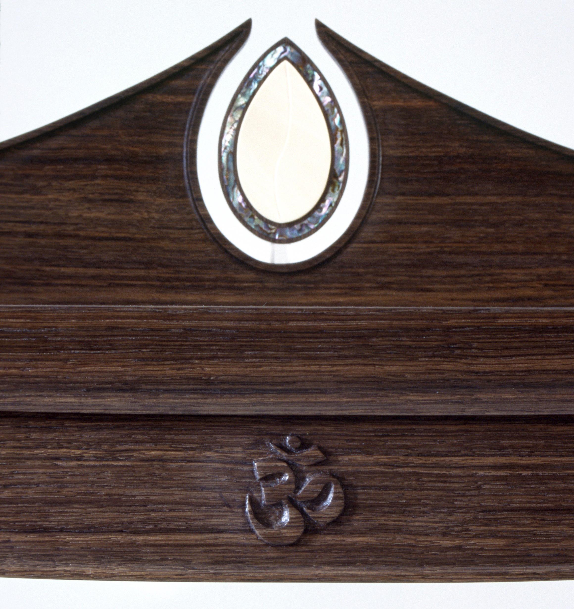 "prayer table (details): green abalone & carved Sanskrit symbol for  ""Om"""