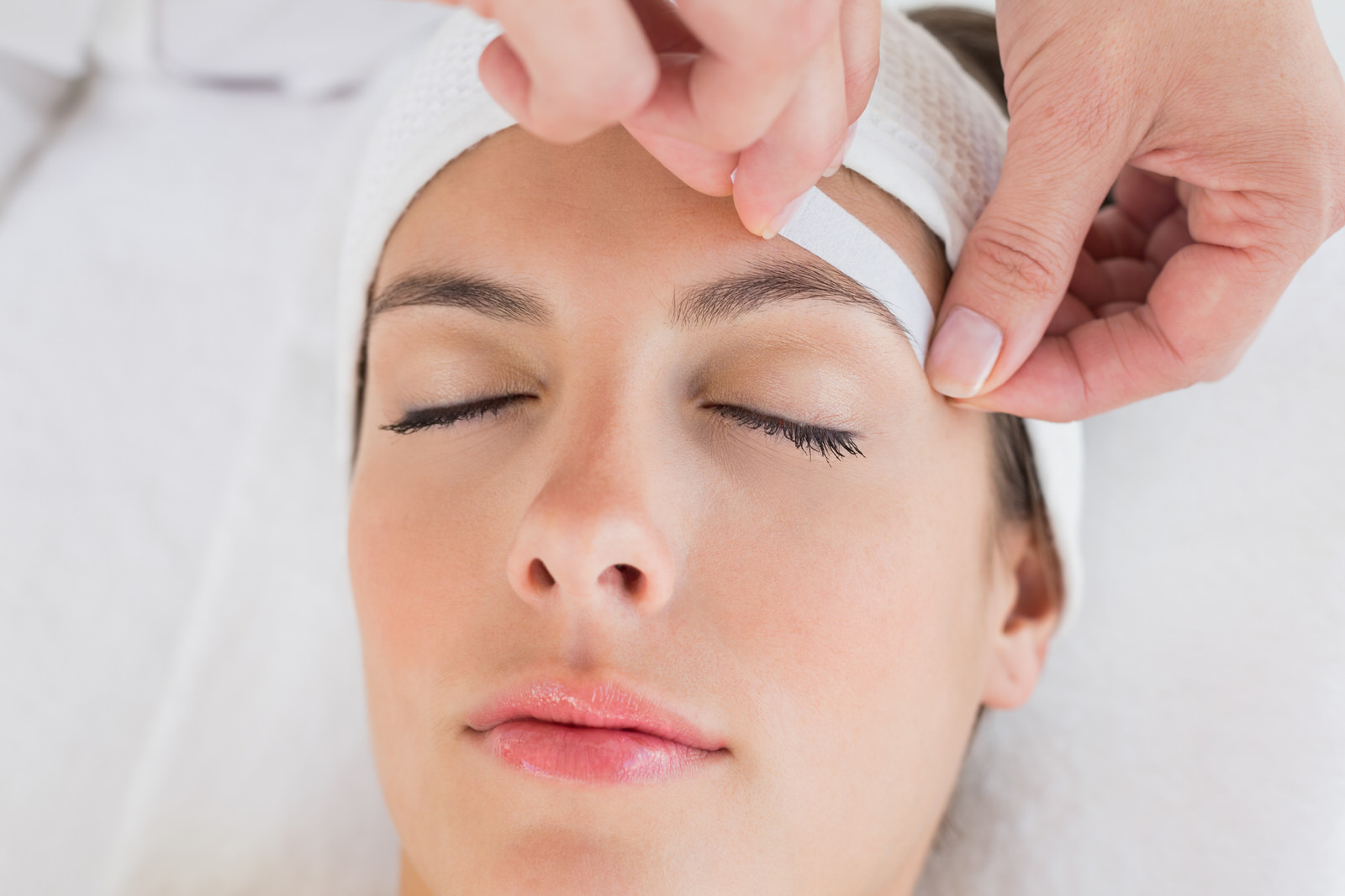 A woman gets her eyebrows waxed at a salon.