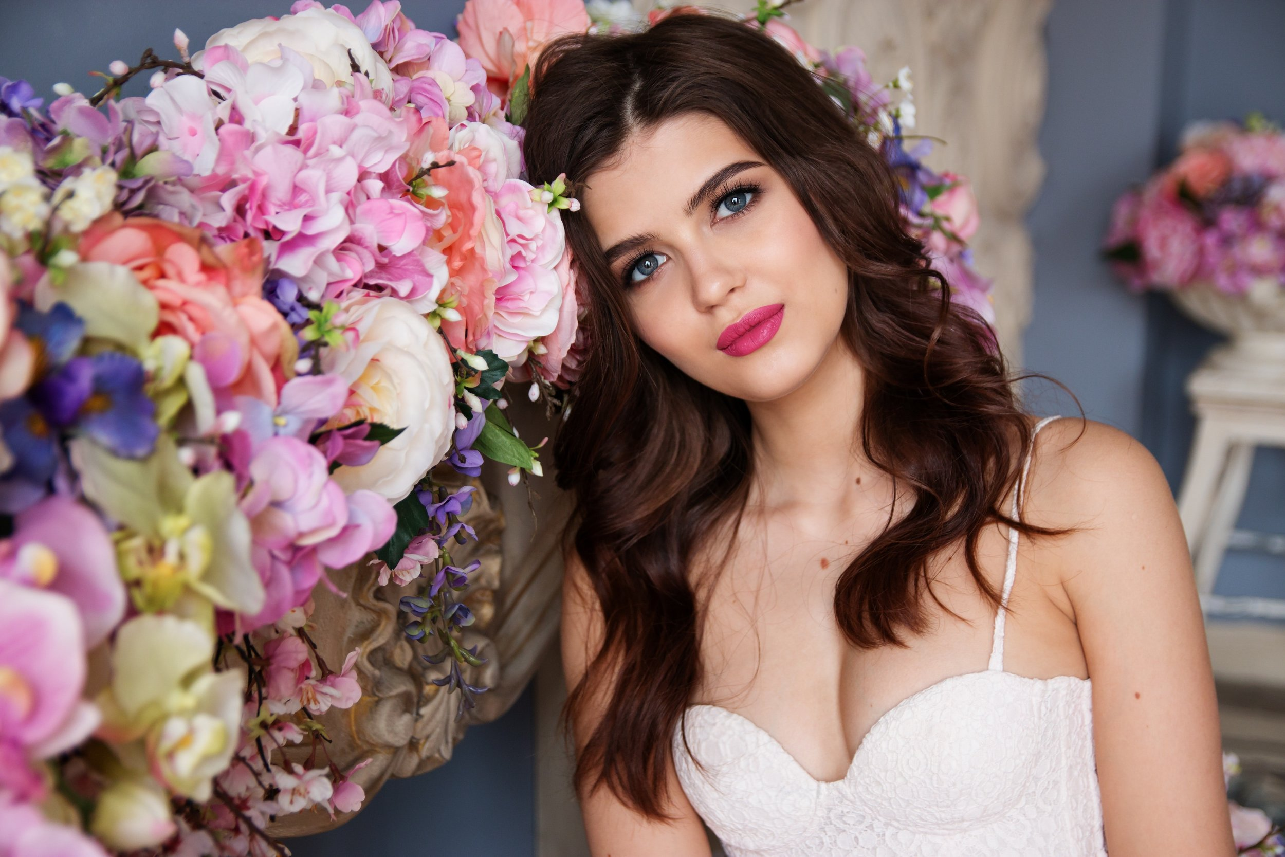 Bride with loose waves standing next to pink flowers