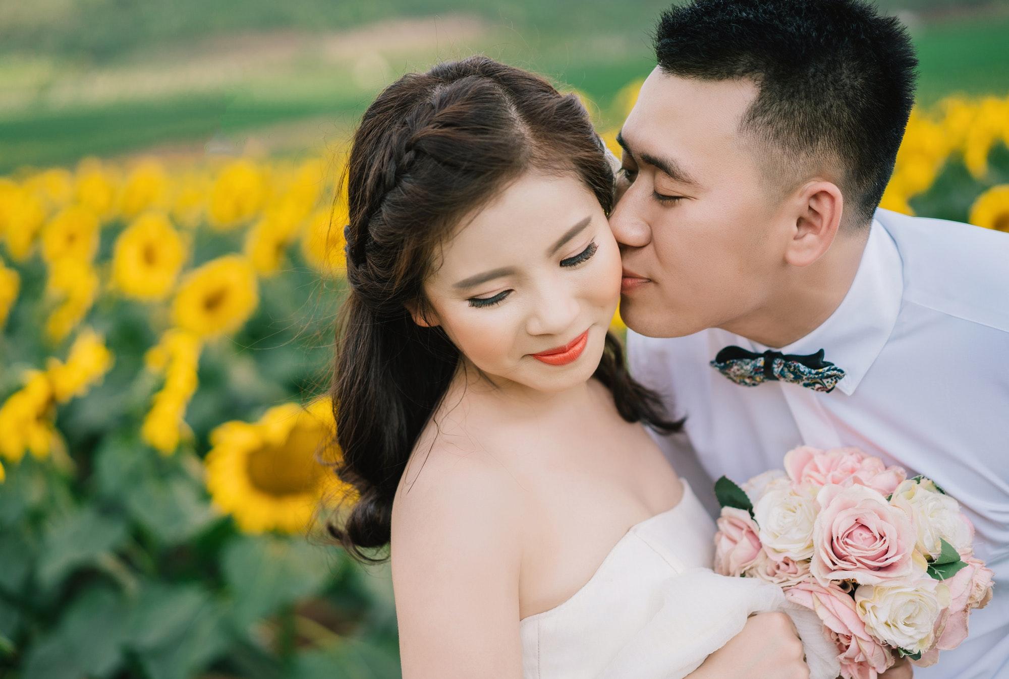 A groom kisses a brides cheek