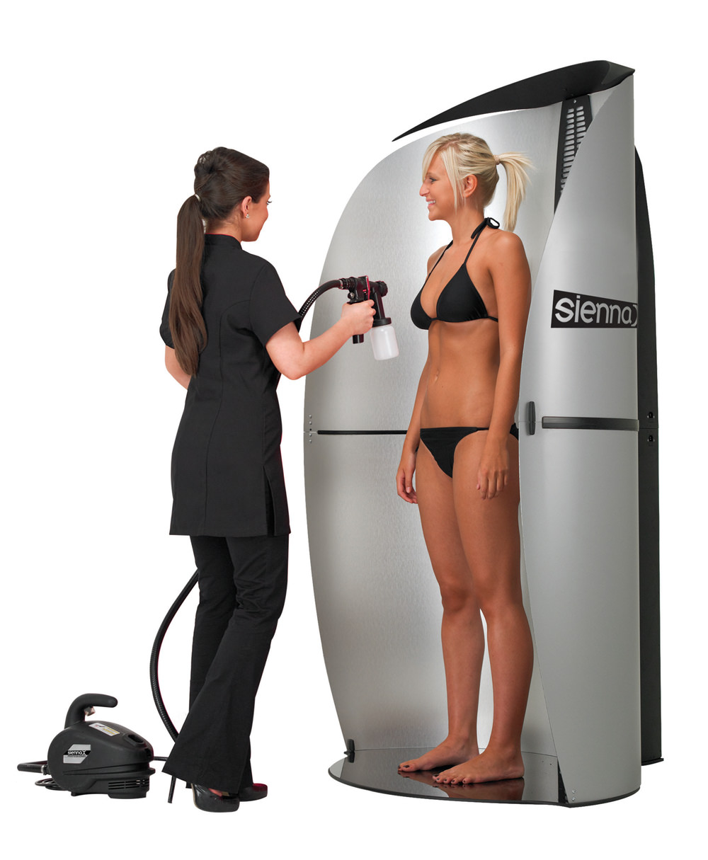 A woman gets a spray tan from a professional