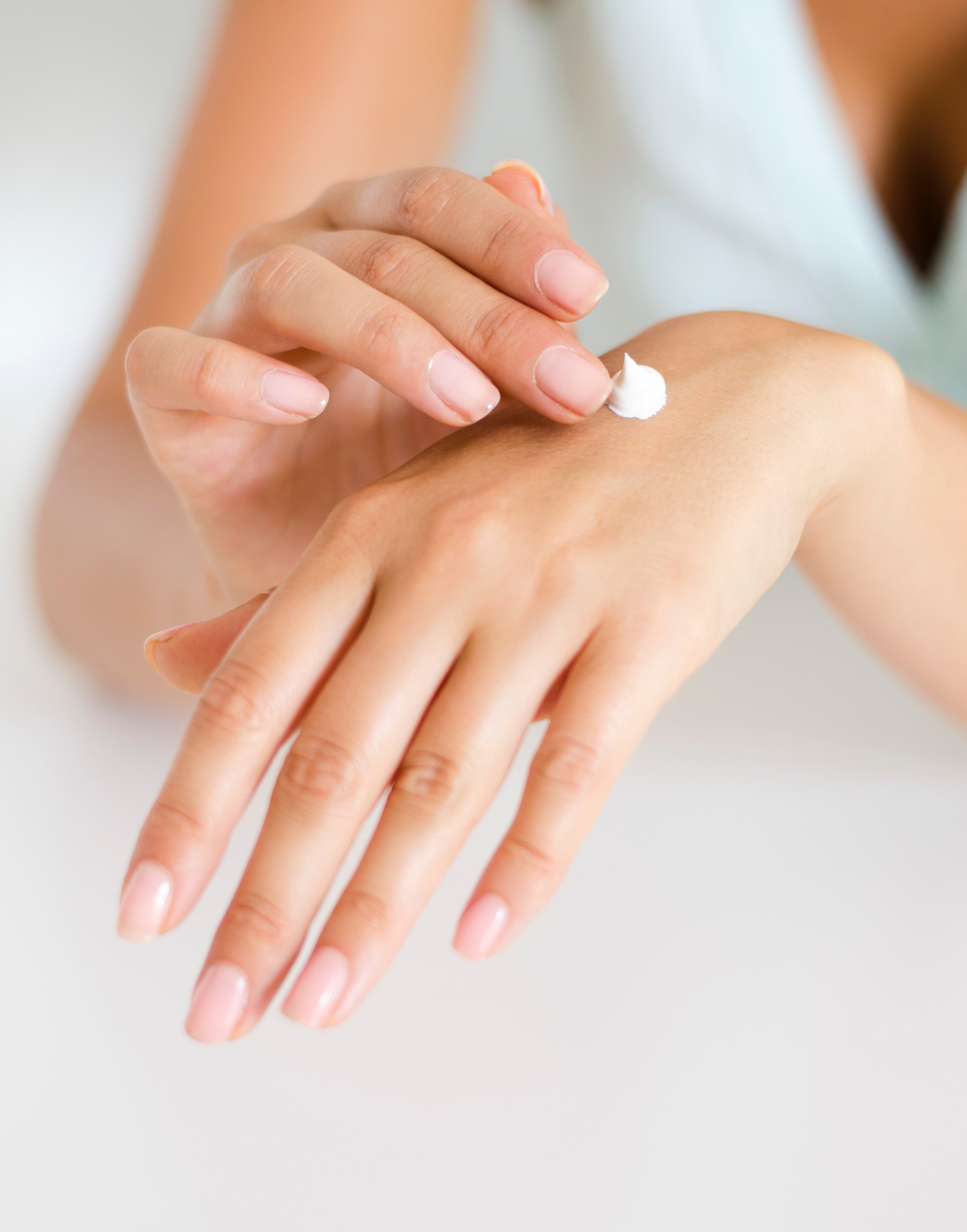 A woman applies lotion to her hands