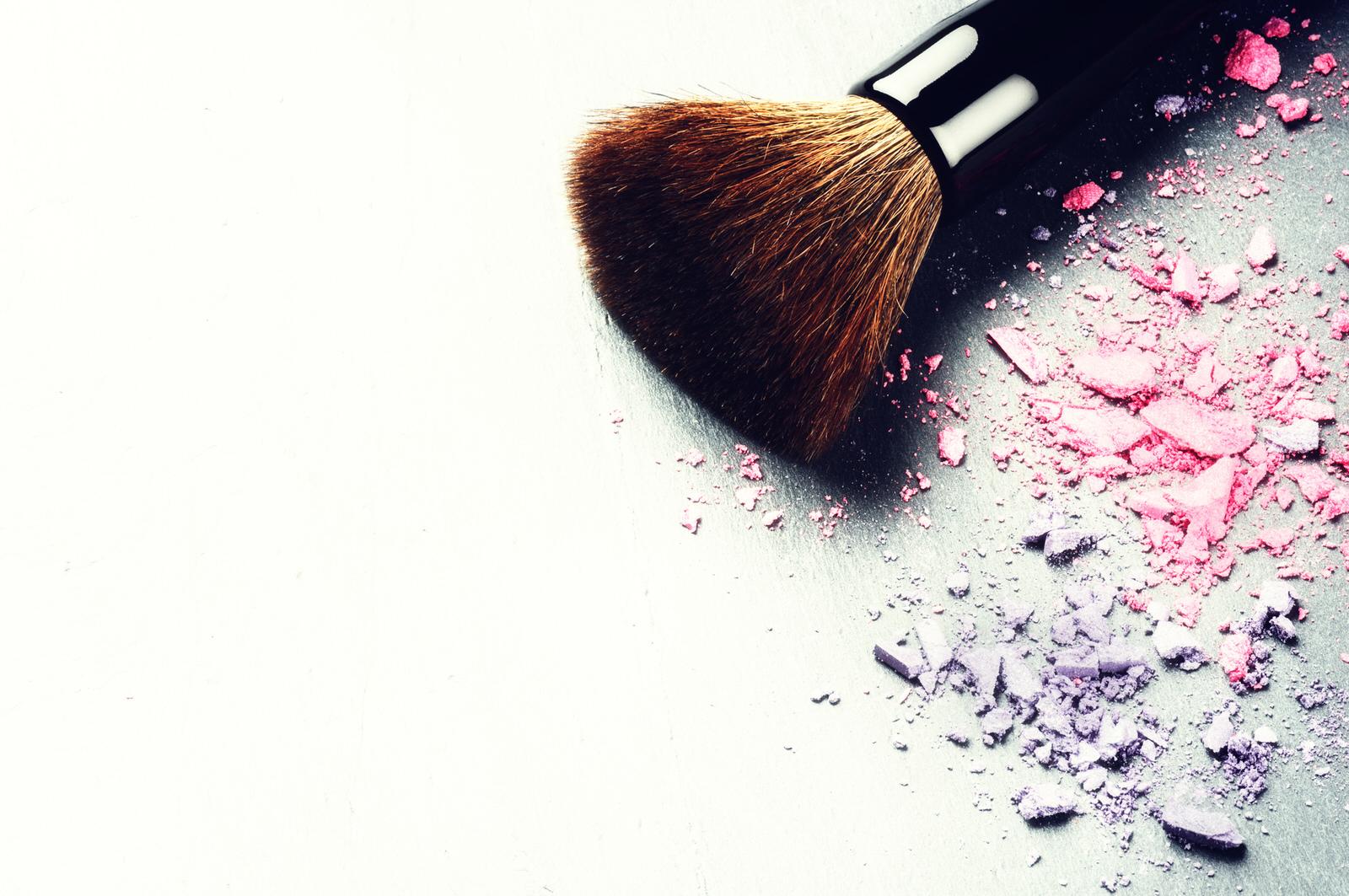 A makeup brush next to crushed makeup