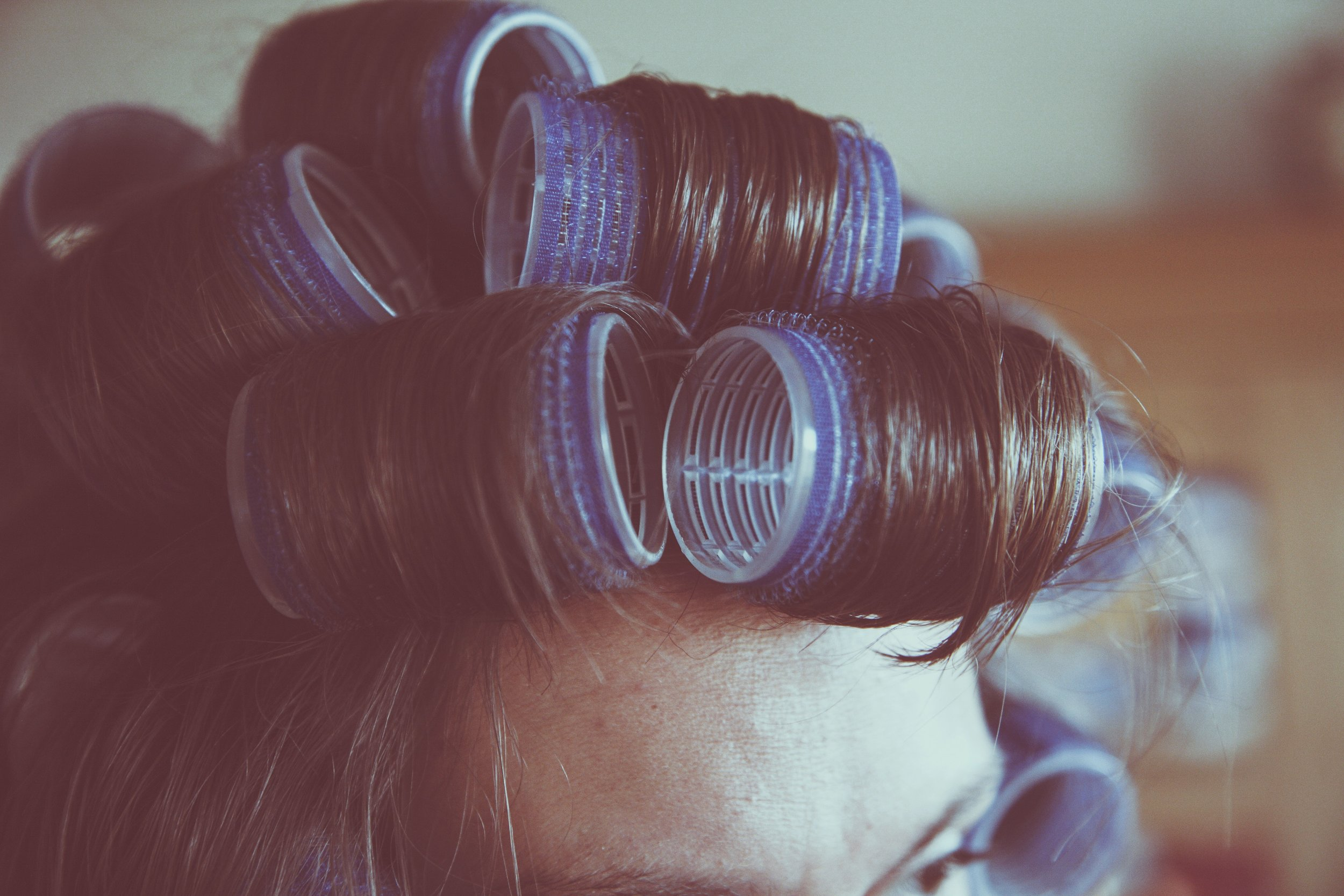 A female with hair curlers in her hair