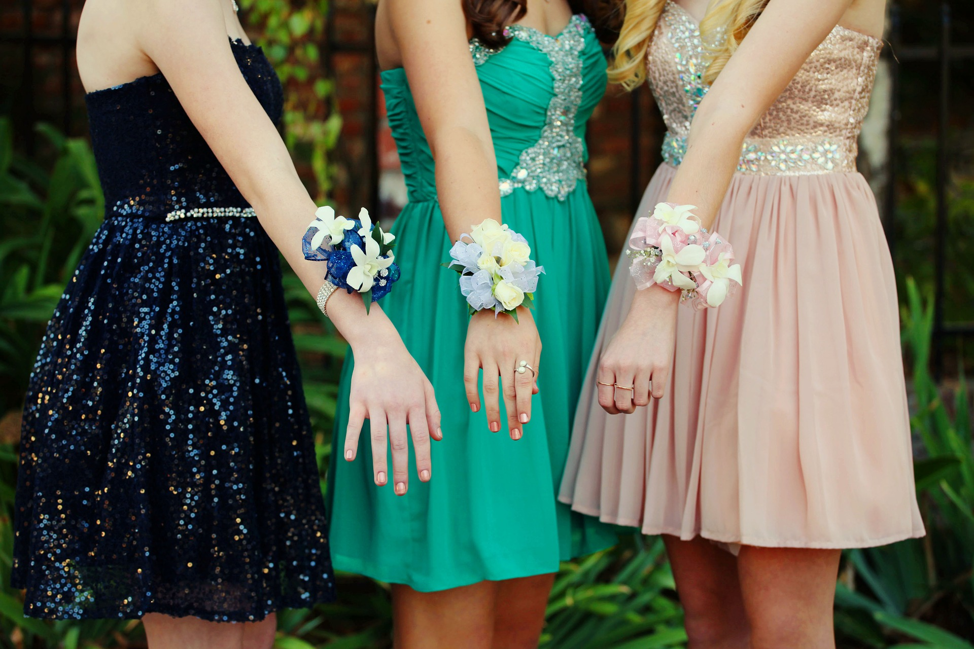 Three girls who have on dresses and corsages.