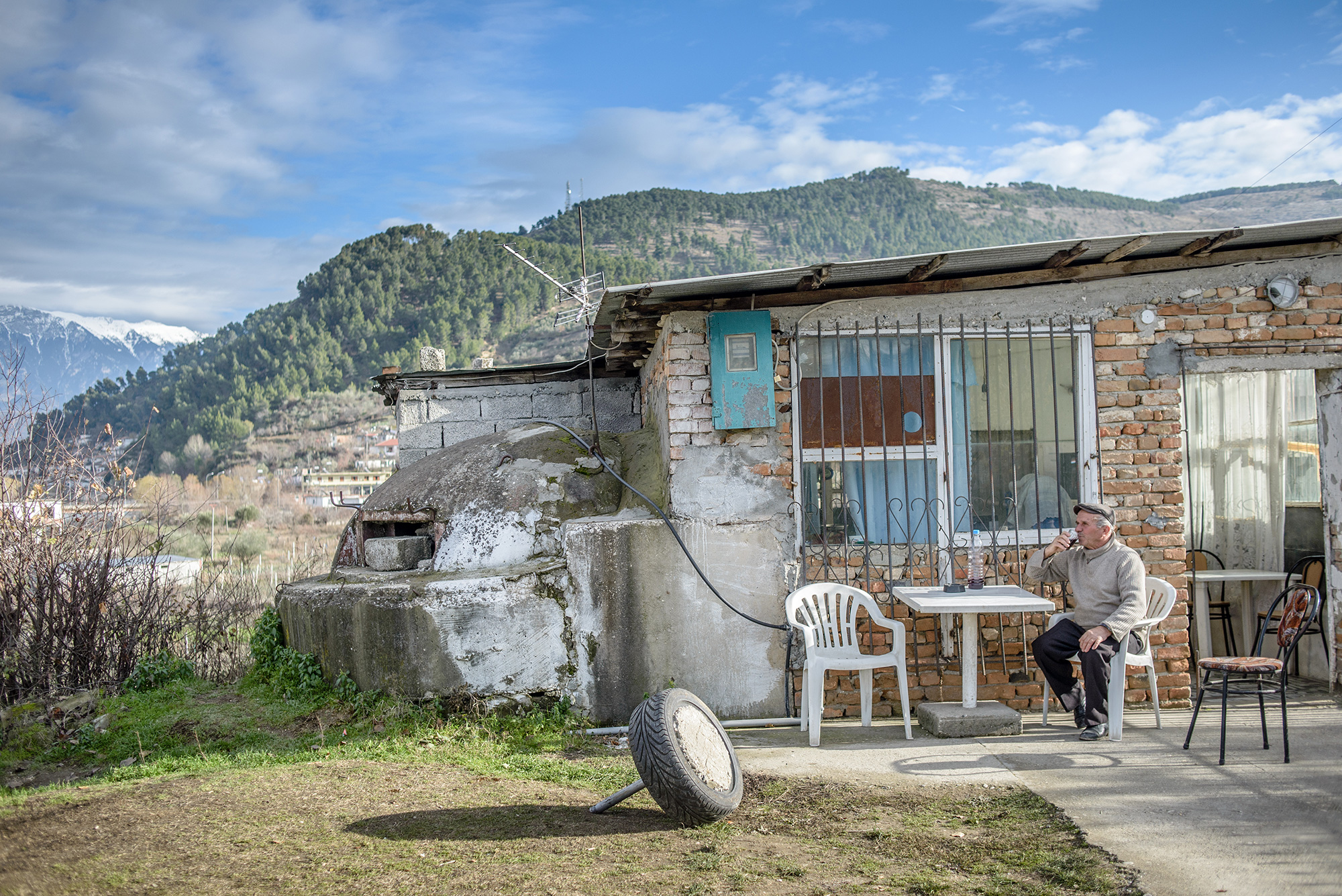 Mr. Bregu, the owner of a cafe drinks wine in the backyard of his cafe, Berat, Albania