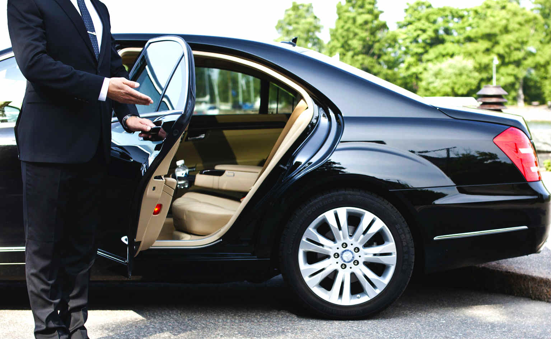 Chauffeur opening car door.