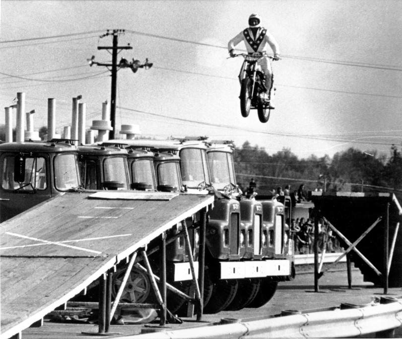 Evel Knievel casually jumping some big old trucks.  Source