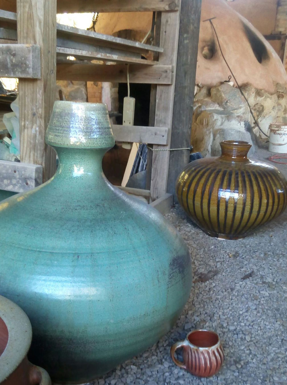 Large vessels, a mug, and the kiln in the background - all by Mark
