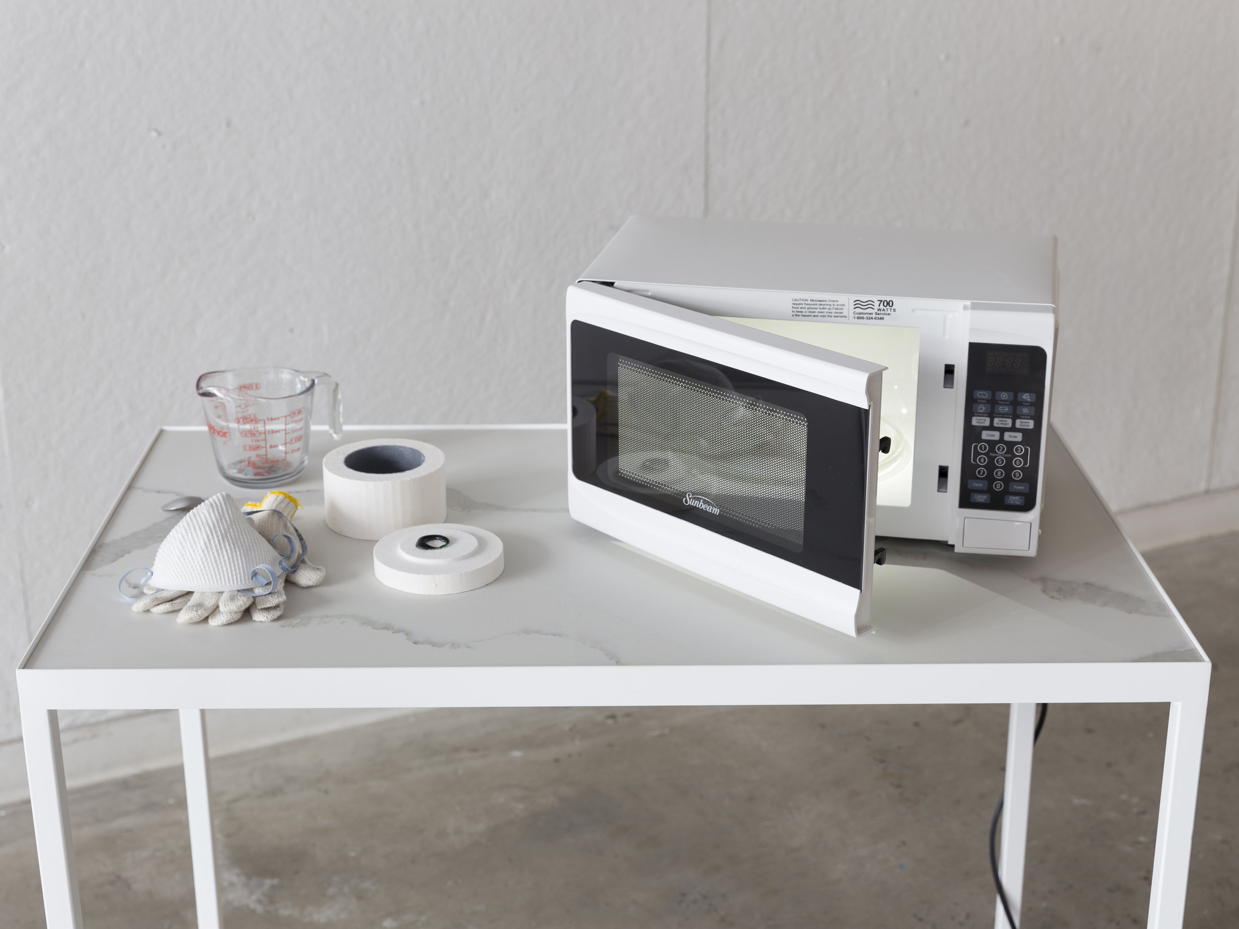"Station 3 detail   Microwave, microwavable kiln, gloves, dust mask, measuring cup, glass shards, microwaved chakra, spoon ,  quartz, iron 50"" x 24"" x 40""   Photo credit:  Jonathan Allen"