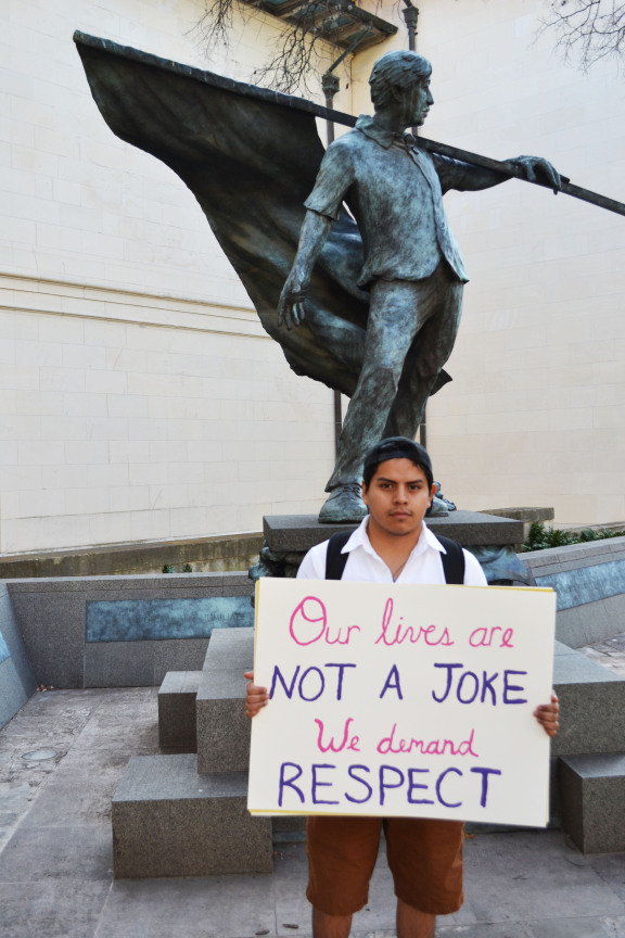 Jose Ramirez, first year business and an intern for UT Latinos, helps arrange the United Against Racism March in Austin, Texas on February 12, 2015. The group organized in front of the Cesar Chavez statue with their handmade posters before marching to the Phi Gamma Delta (FIJI) house.