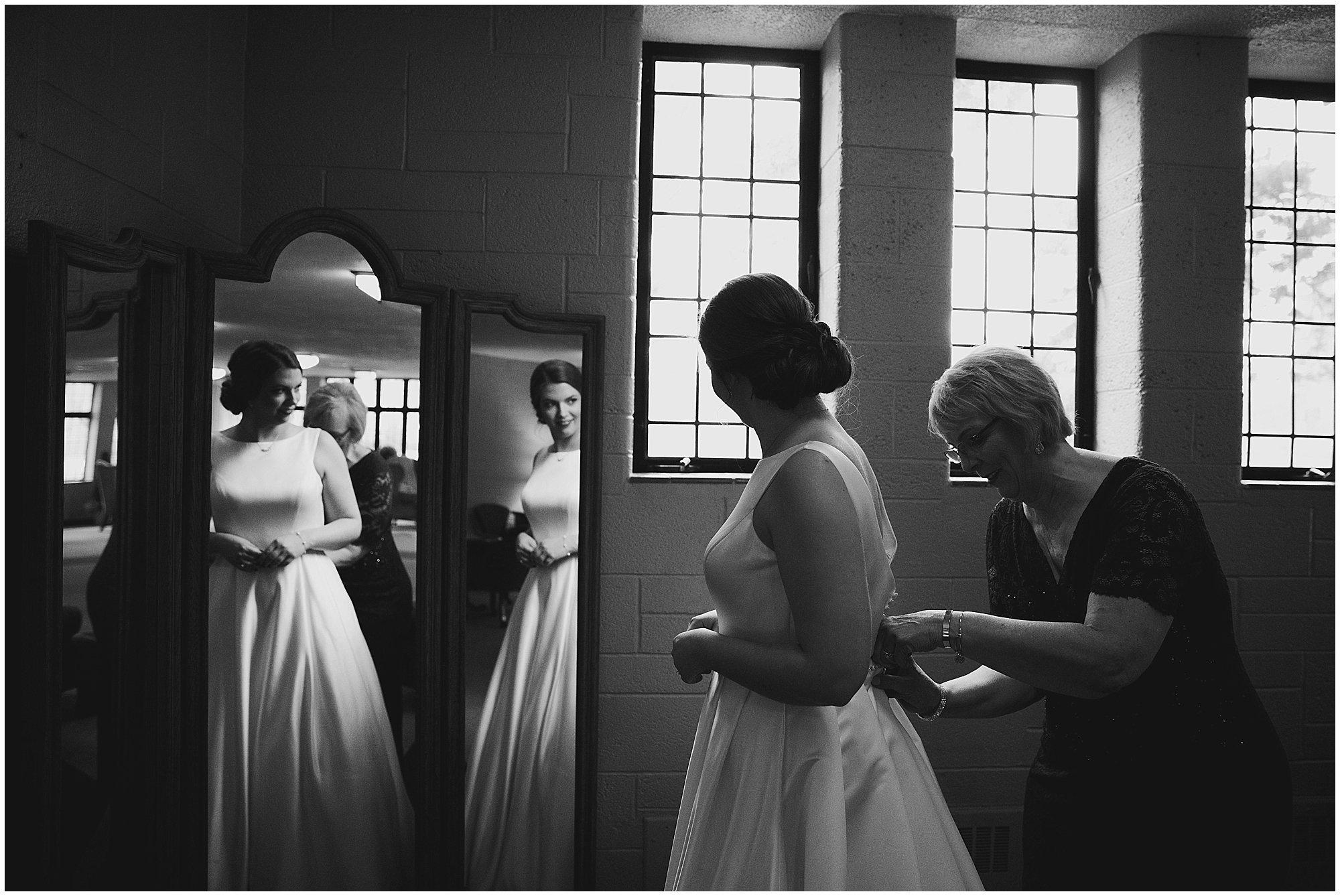 bride getting into wedding dress mirror